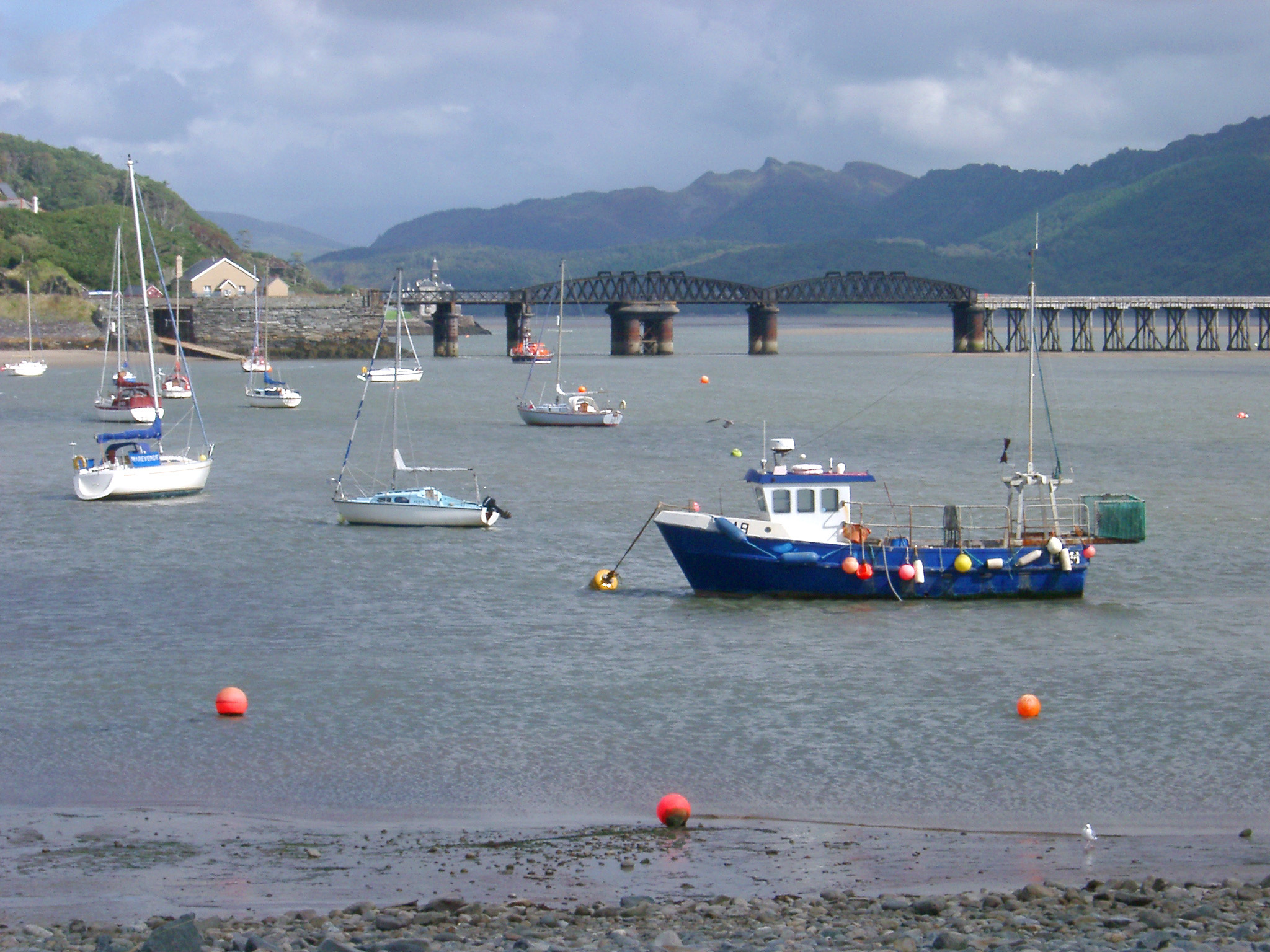 Fishing boats moored in the harbour at Barmouth with the viaduct carrying the railroad crossing the water in the background , Gwynedd, Wales