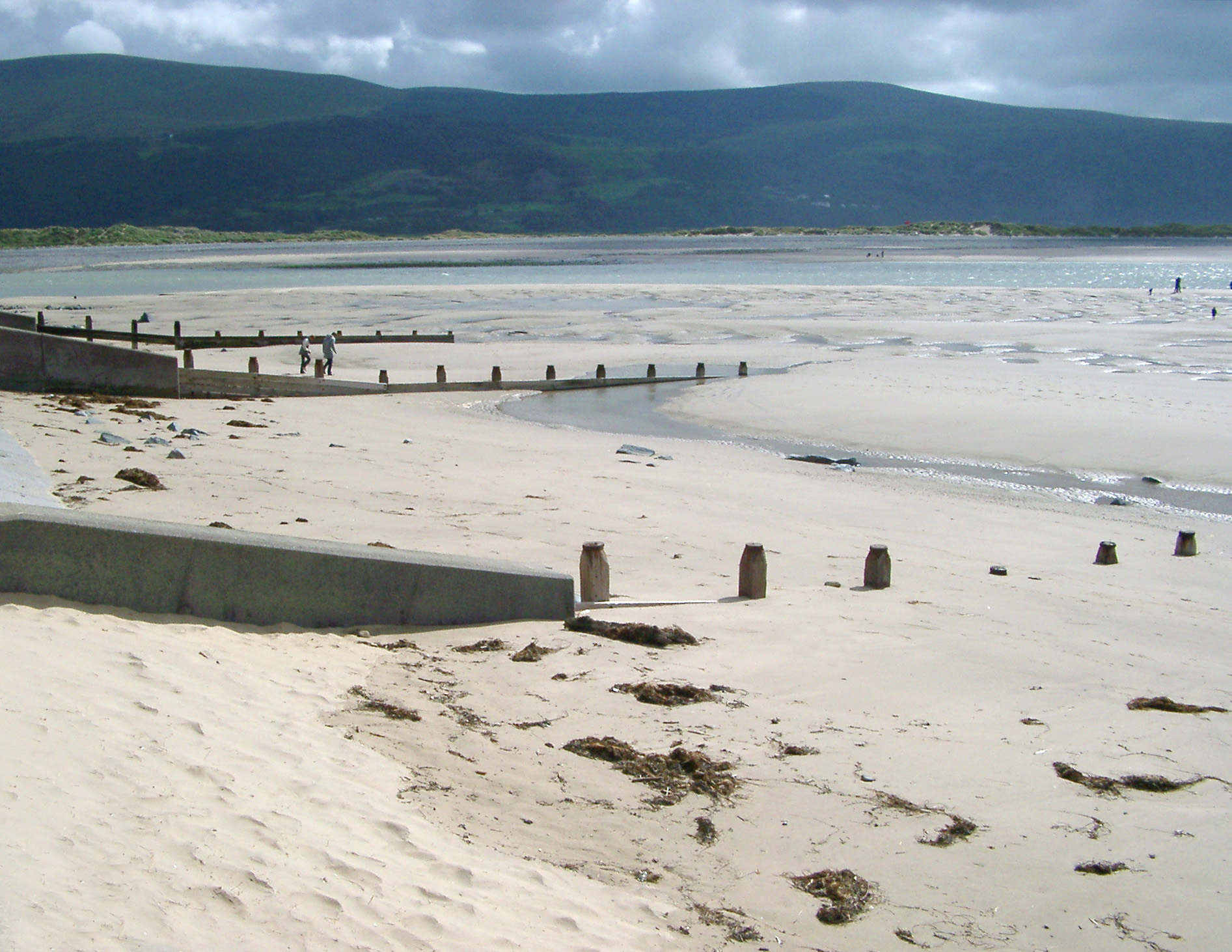 Wooden groynes in the sand on the beach at Barmouth, Wales built to control coastal erosion from the tides