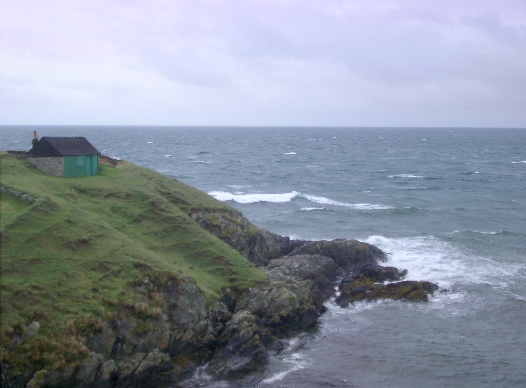 Rocky headland with the roof of a seafront cottage just visible jutting into a calm ocean on an overcast cloudy day