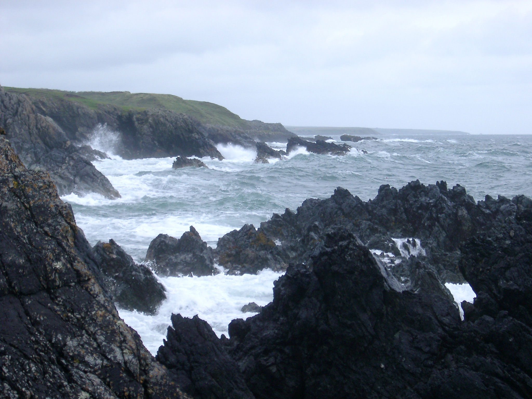 Stormy sea with waves pounding a rocky coastline on an overcast misty day