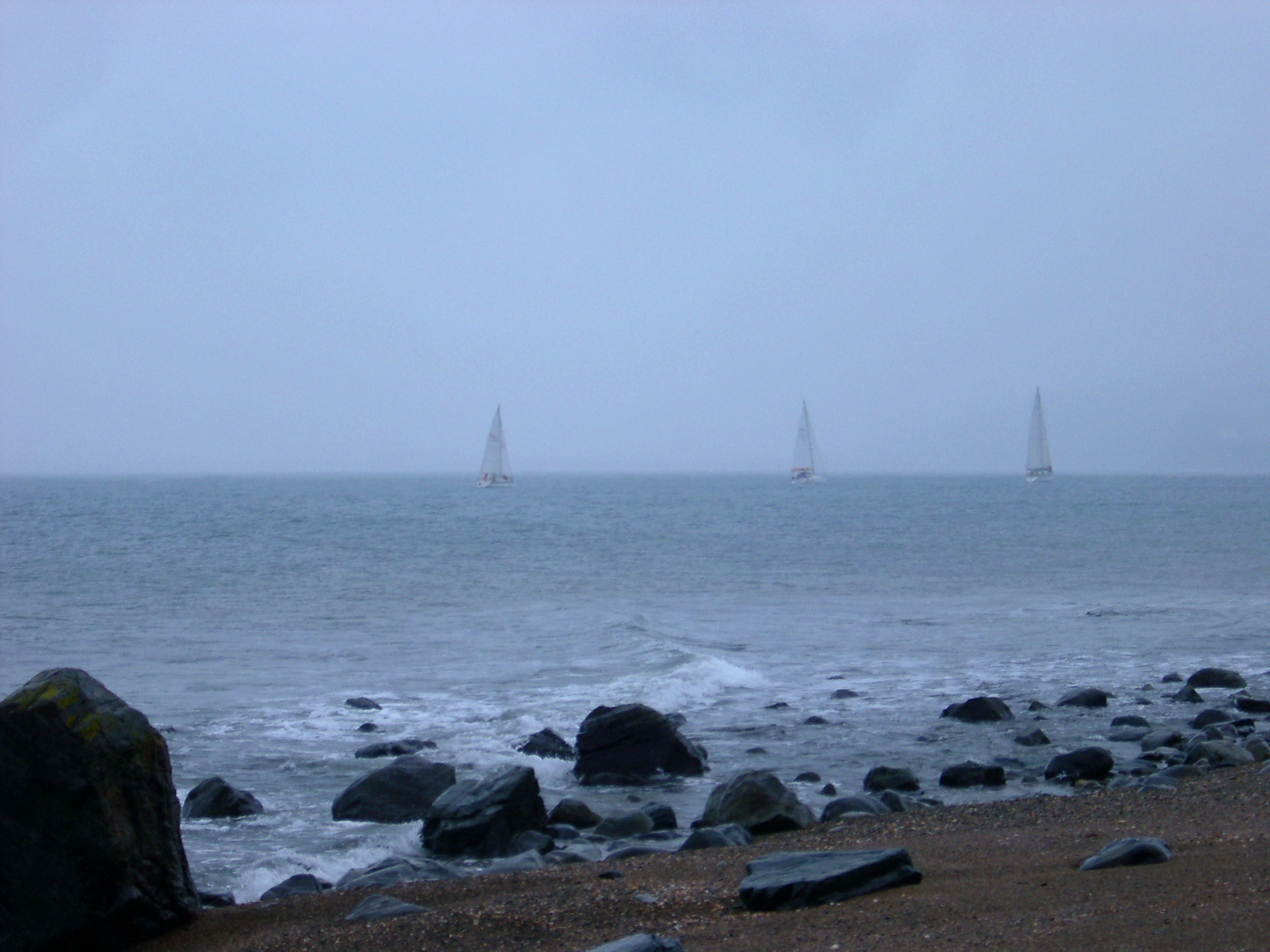 View from a rocky beach of three yachts sailing offshore on the horizon on a cold bleak misty day