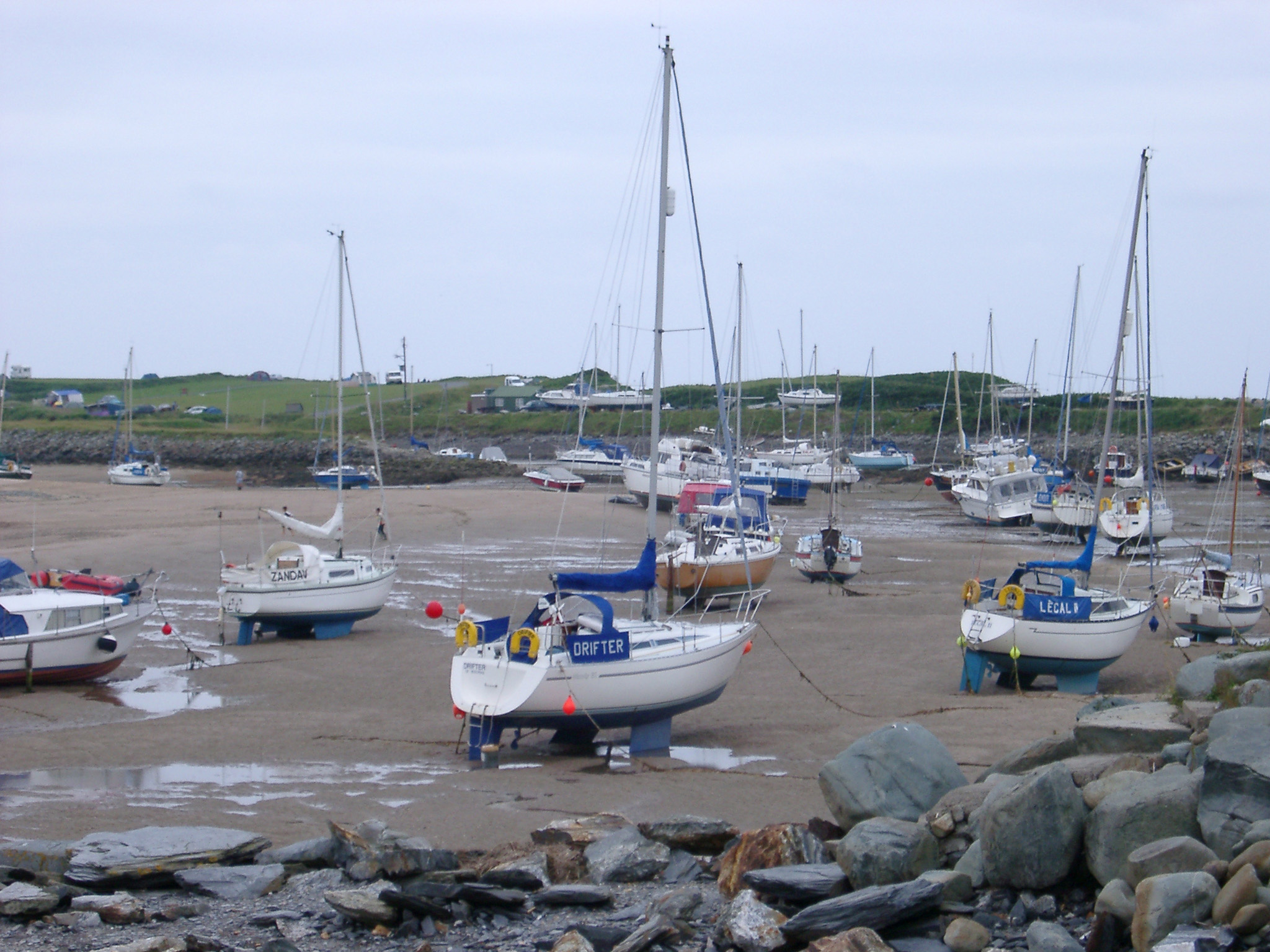 Boats in a tidal harbor beached high and dry on the sand as the tide has gone out in the estuary in Shell Island, UK