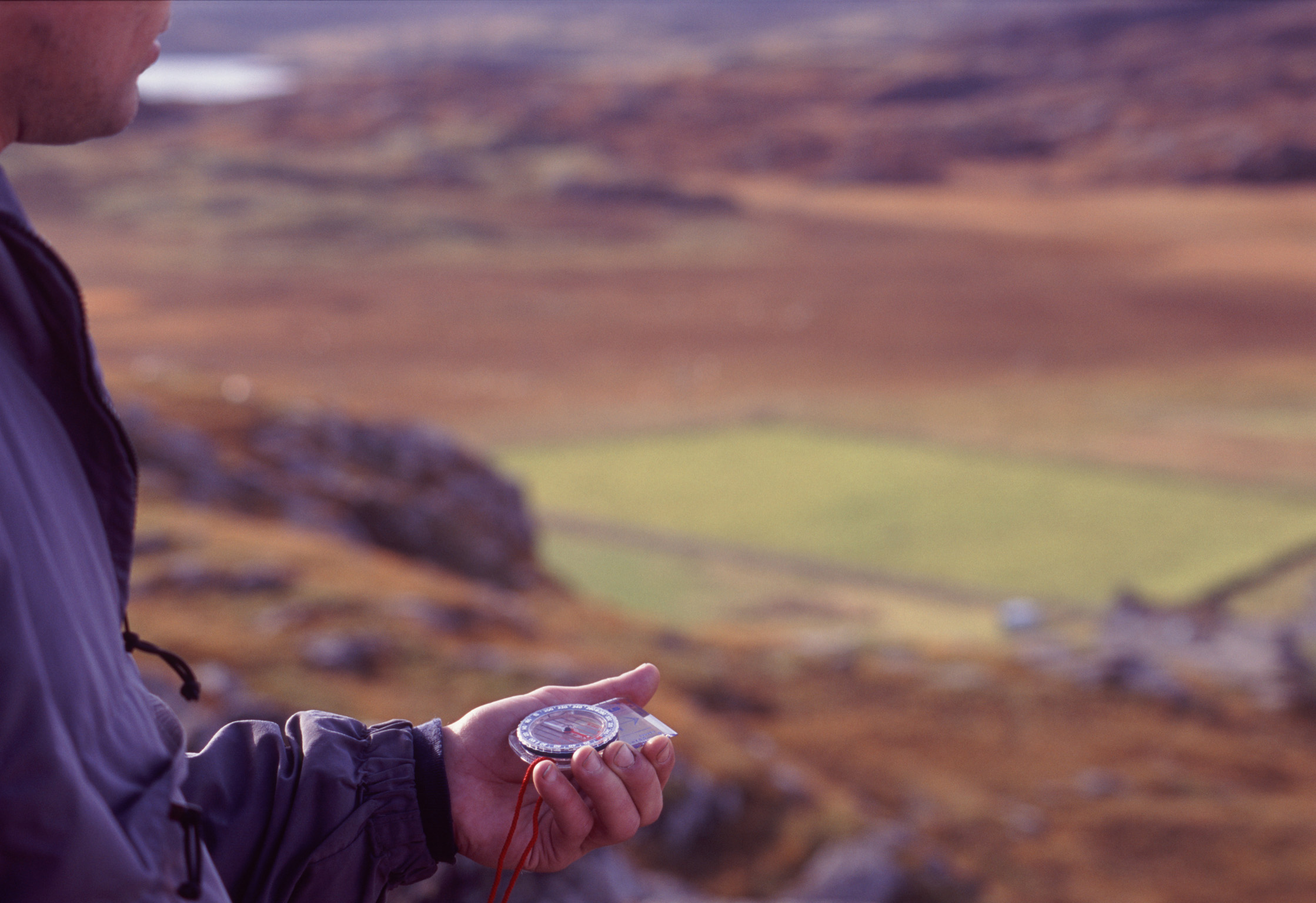Man holding a compass in his hand when out walking in the mountains of Scotland to navigate using magnetic north