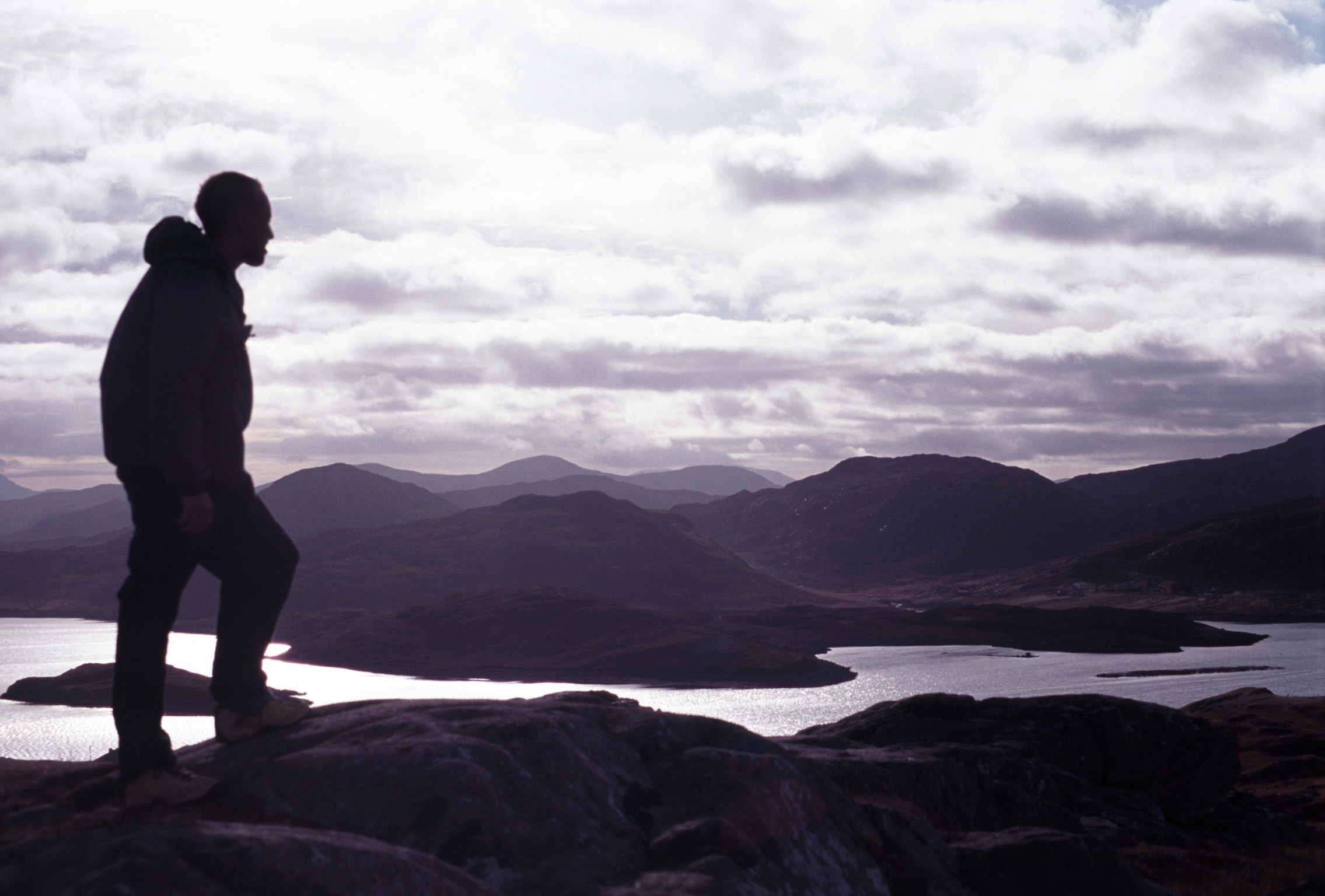 Climber silhouetted on a mountain peak overlooking a scenic landscape with lakes at dusk against a cloudy sky