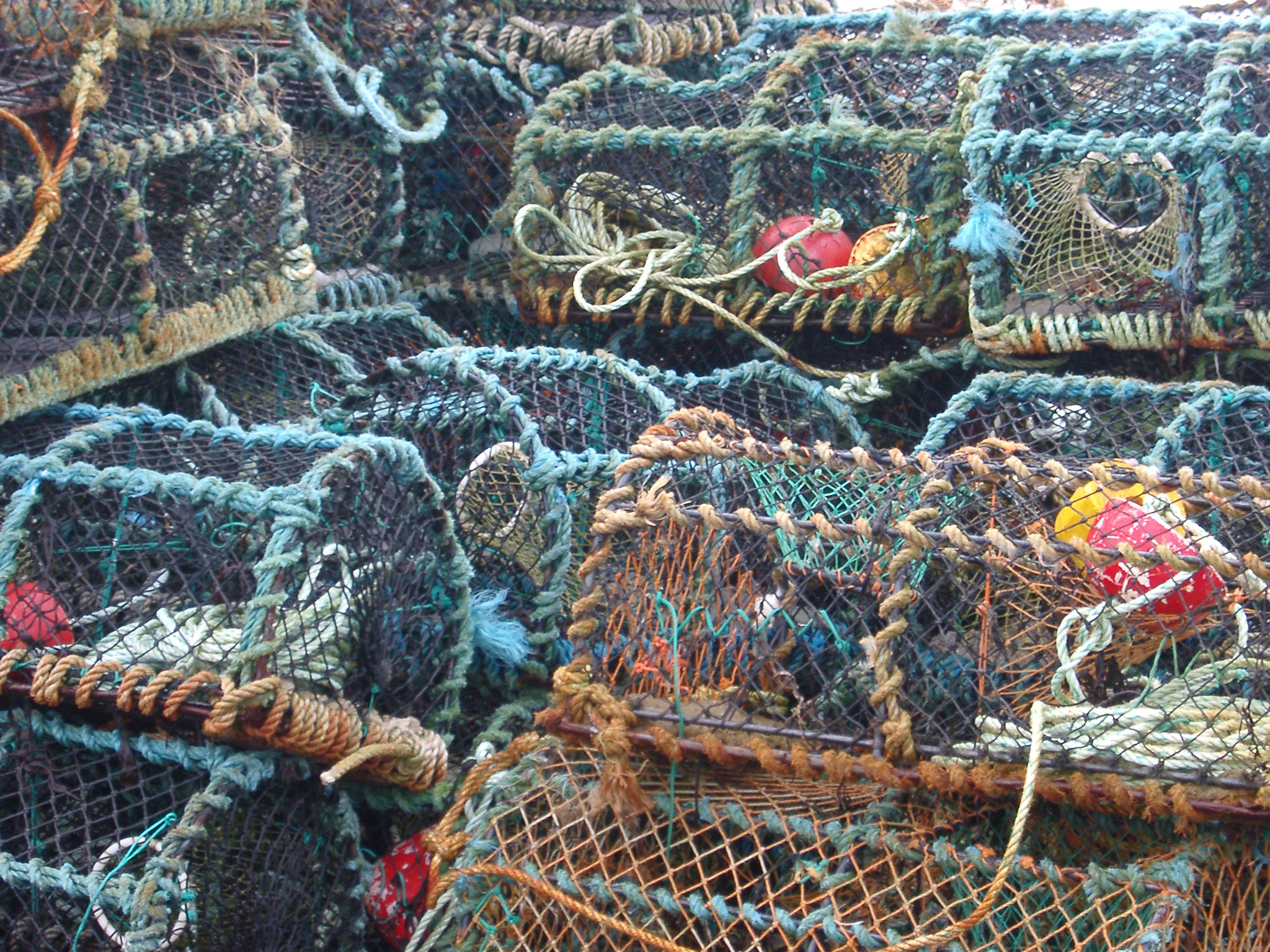 Background of old cylindrical wire mesh crab or lobster pots piled ashore waiting to be lowered into the sea for fishing
