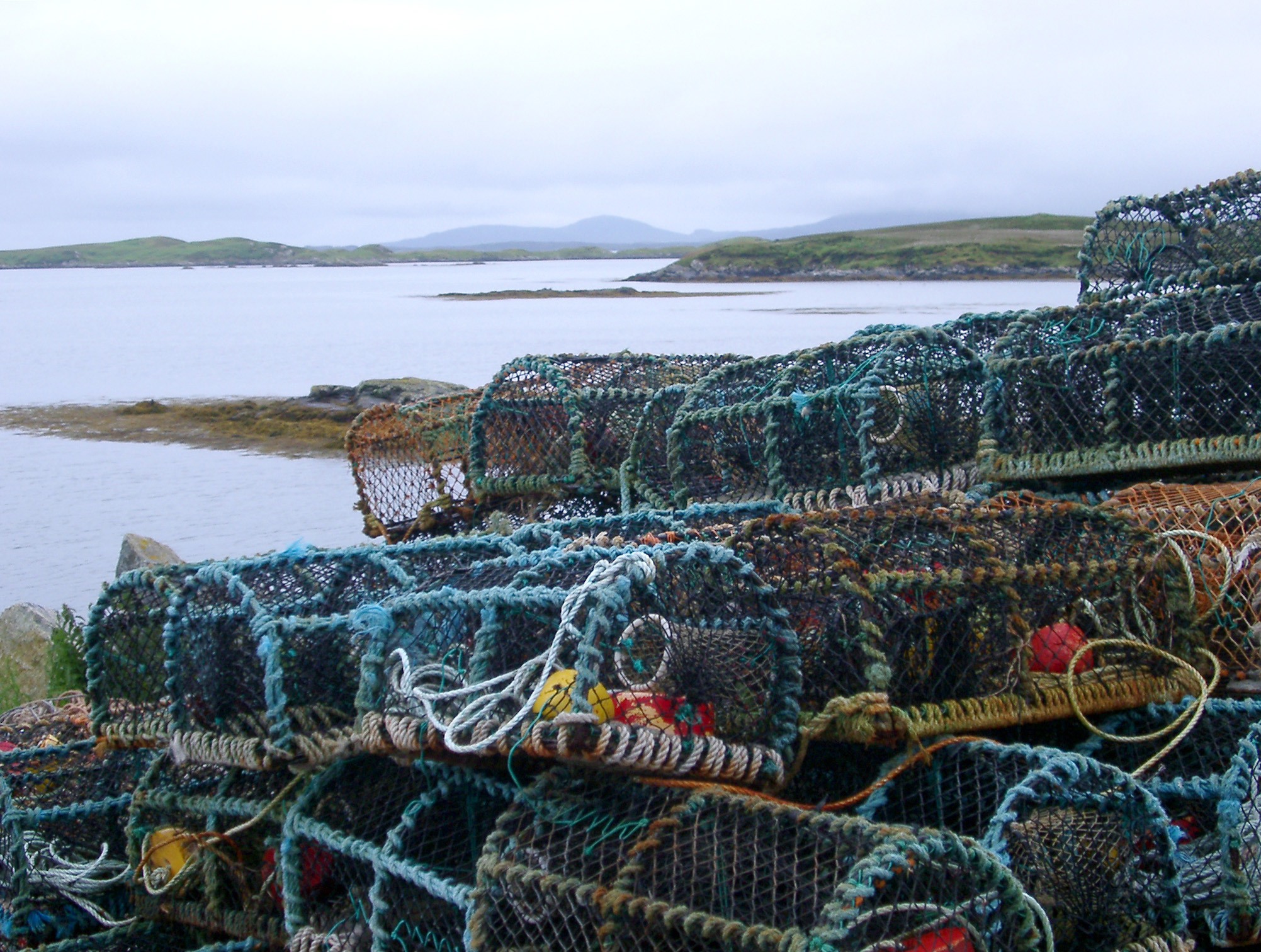 Wire mesh crab pots stacked on the seashore of a loch in Scotland
