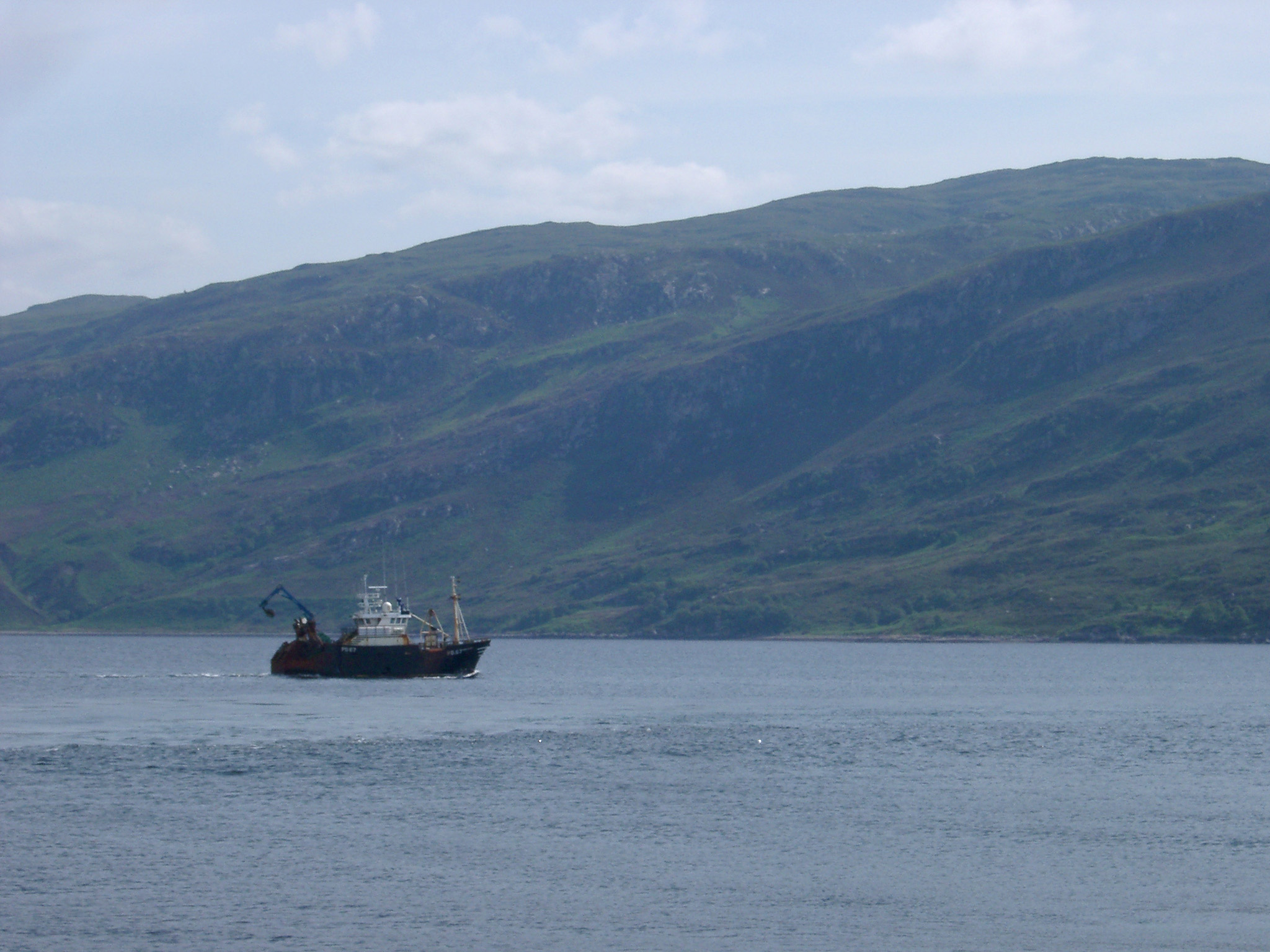 Commercial Fishing Sea Trawler on Scottish Loch with Hills in Background