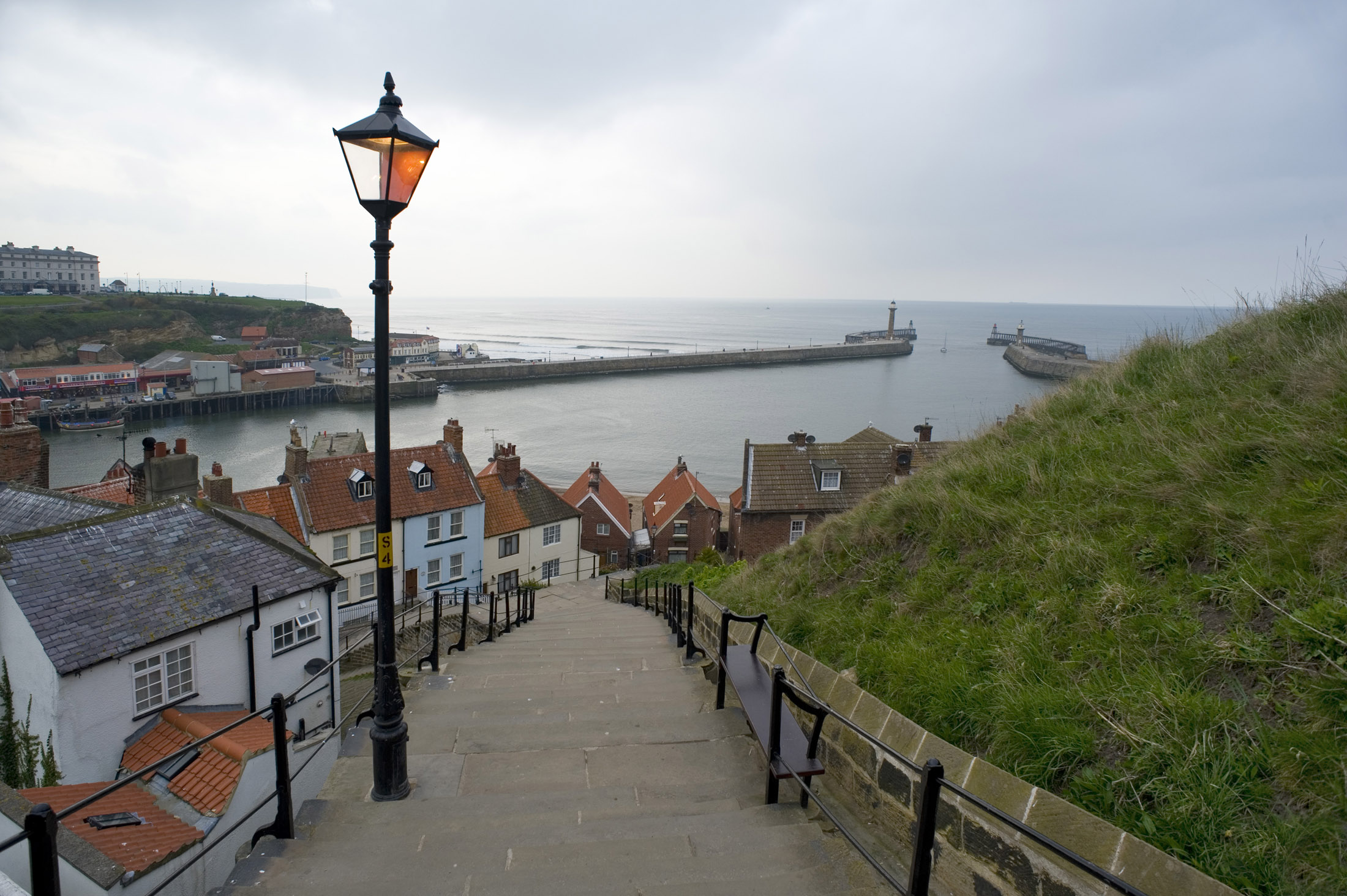 a view down whitbys famous 199 steps towards the harbour seawalls and town