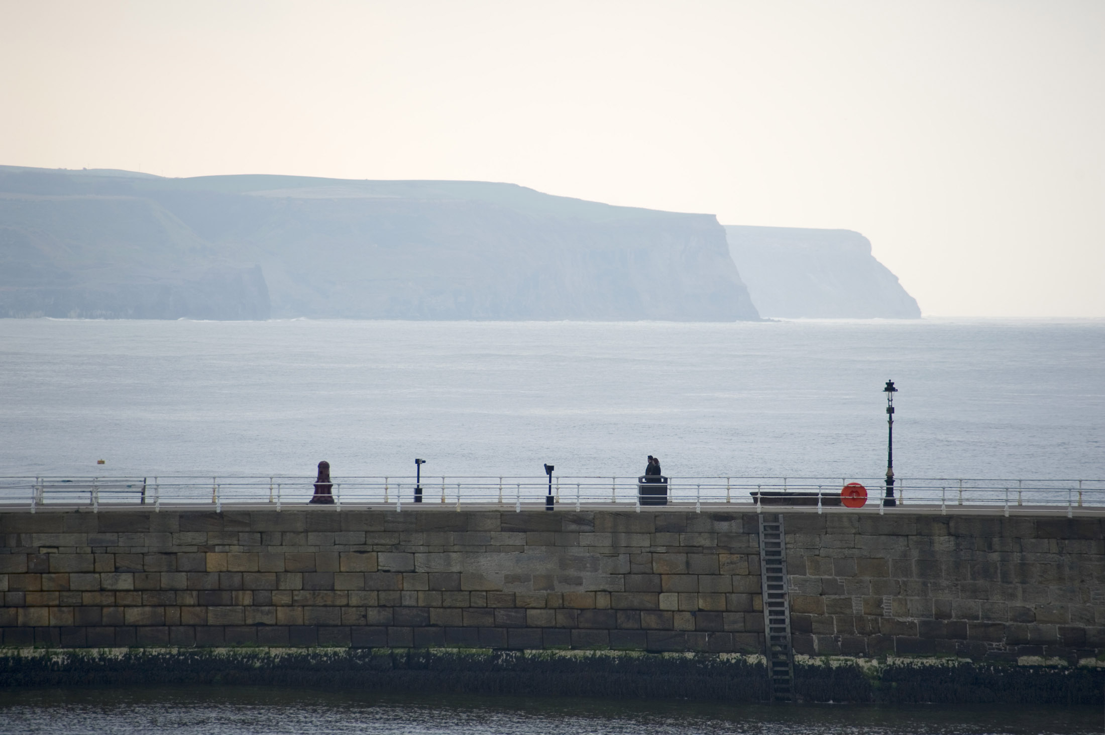 a view across one of the stone piers at whitby an the coastal headlands beyond