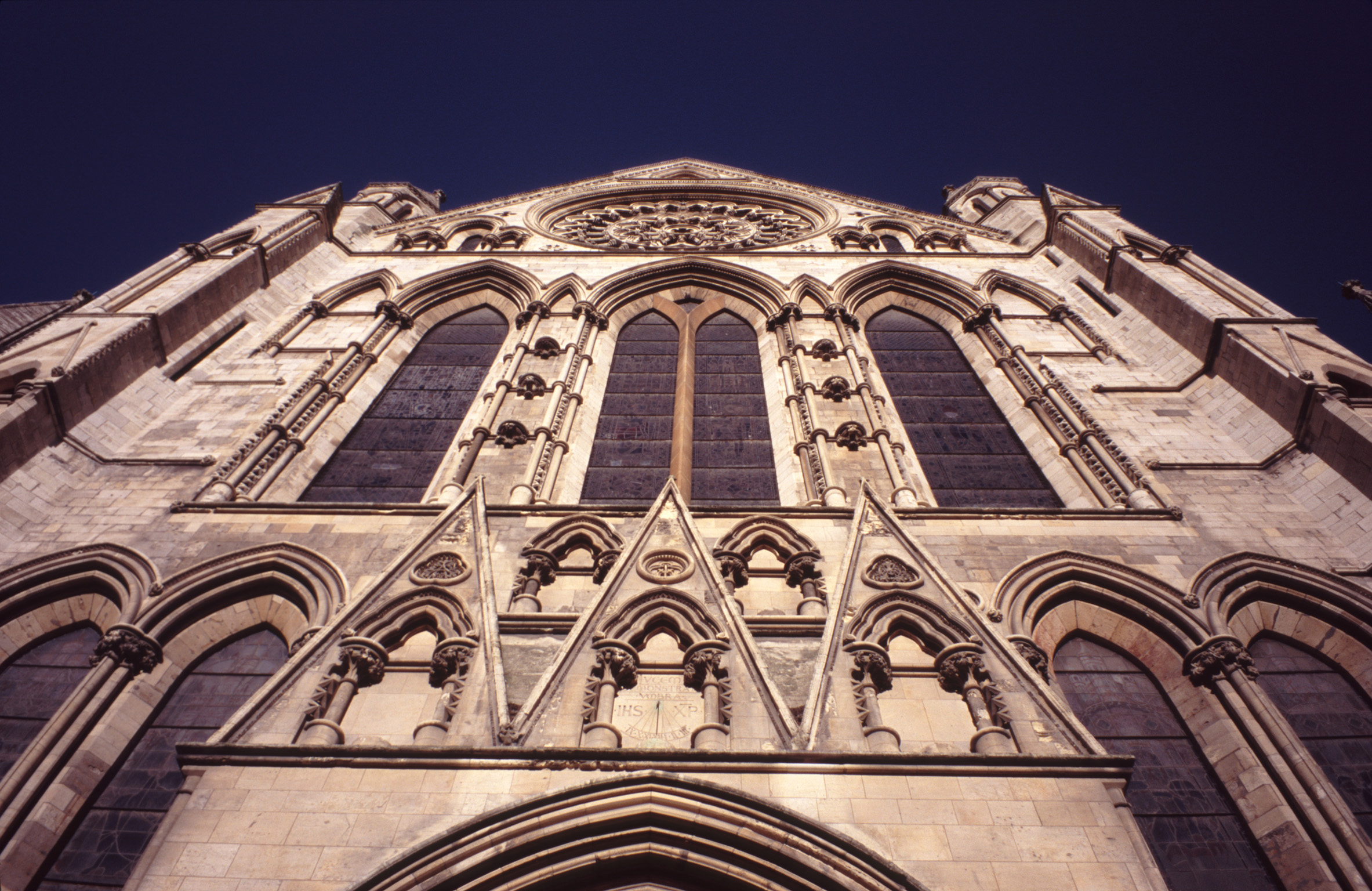 Looking up at the arched windows on the stone exterior facade of York Minster Cathedral, York, UK