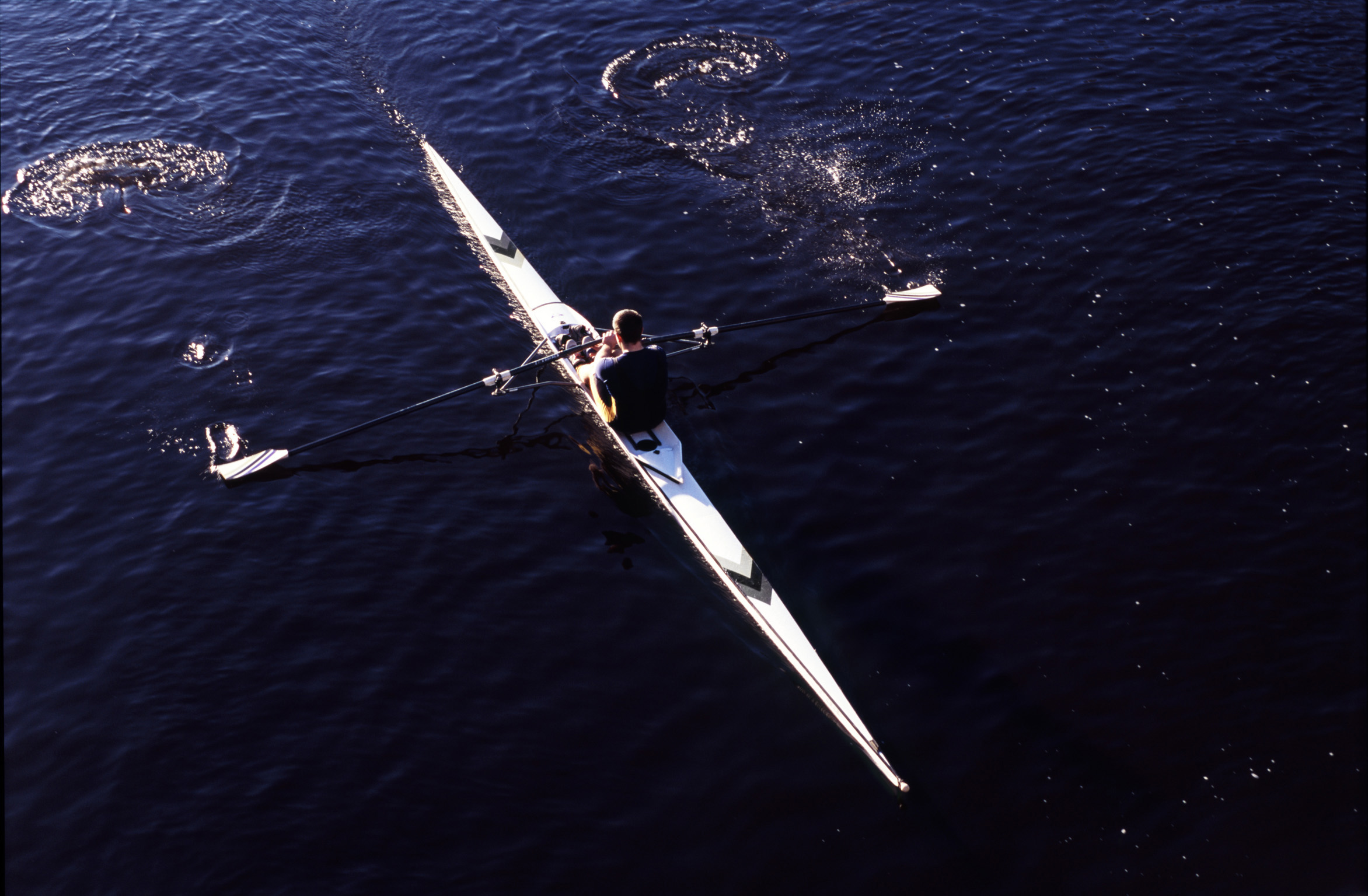 Overhead view of a man practising sculling in a single boat rowing along a river with water splash off the oars
