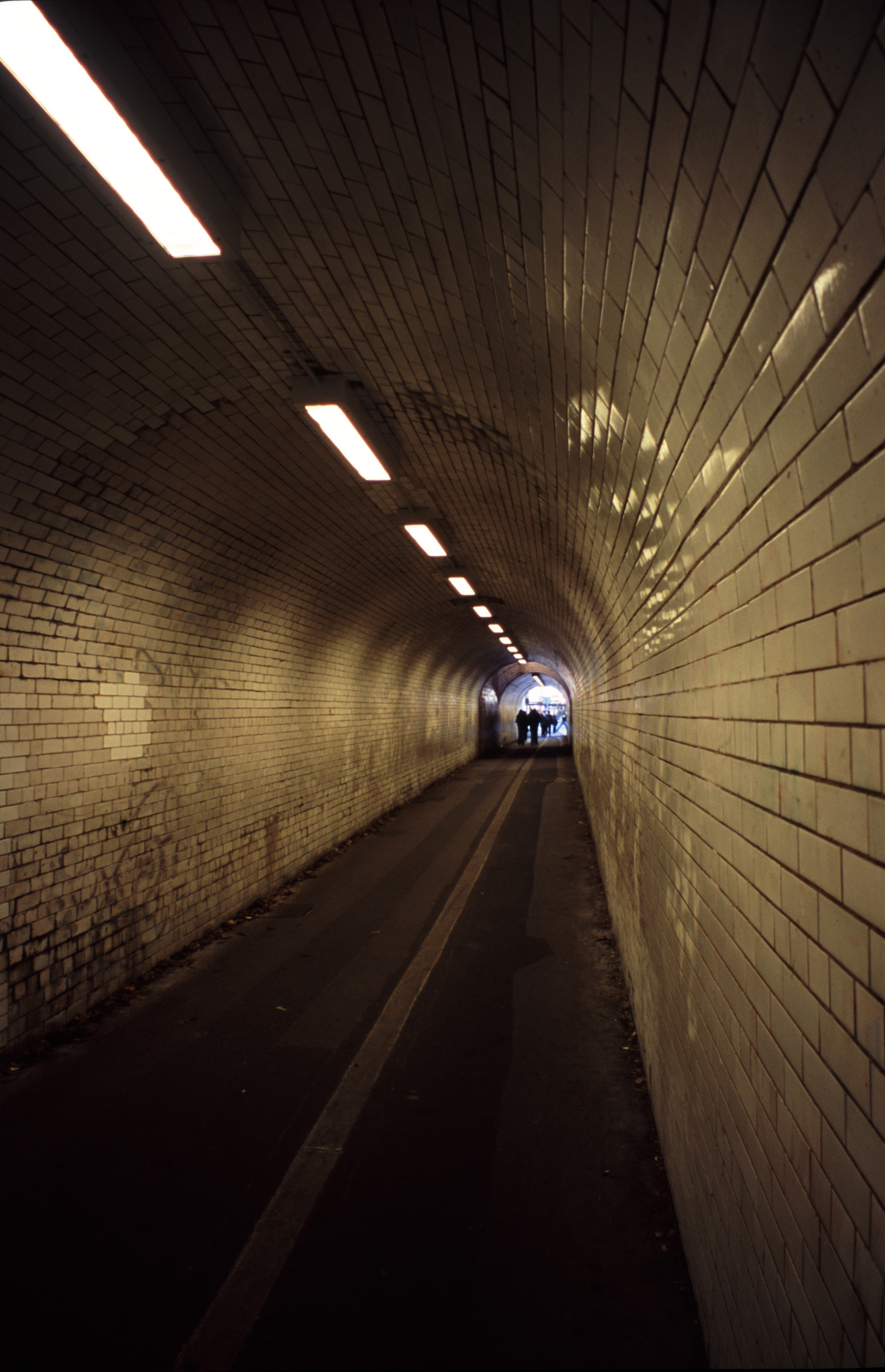 Narrow brick pedestrian underpass lit by overhead fluorescent lights receding into the distance in a straight line