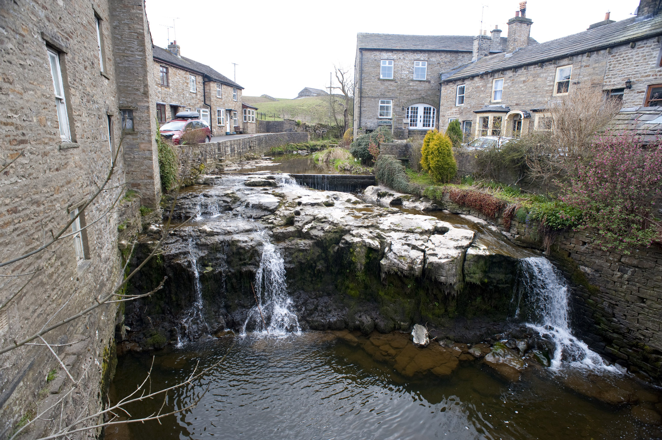 a cascade of water running through the village of hawes