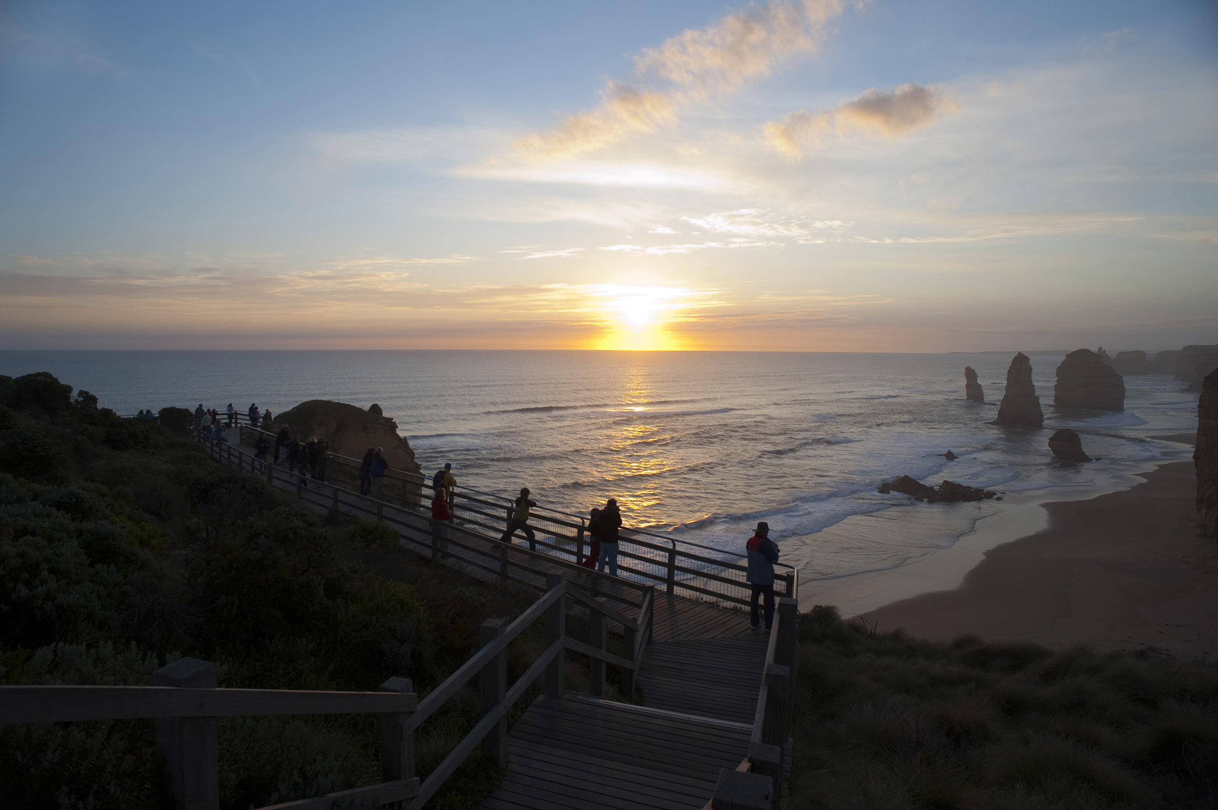 A beautiful hazy sunset over the ocean, coastline, viewing platform and the 12 Apostles on the Great Ocean Road in Australia.