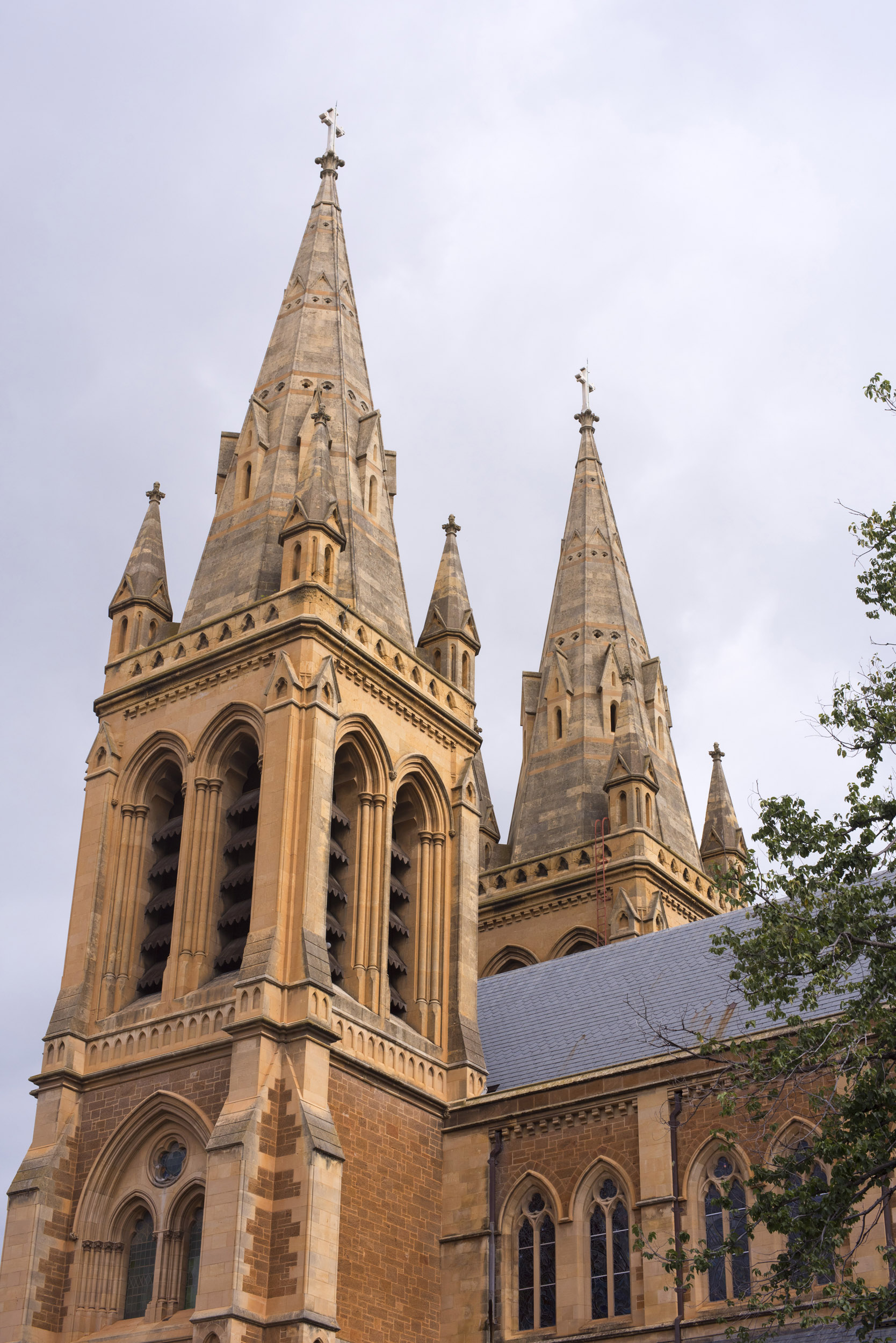 Ornate stone spires of Adelaide Cathedral, Australia against a cloudy grey sky viewed from below