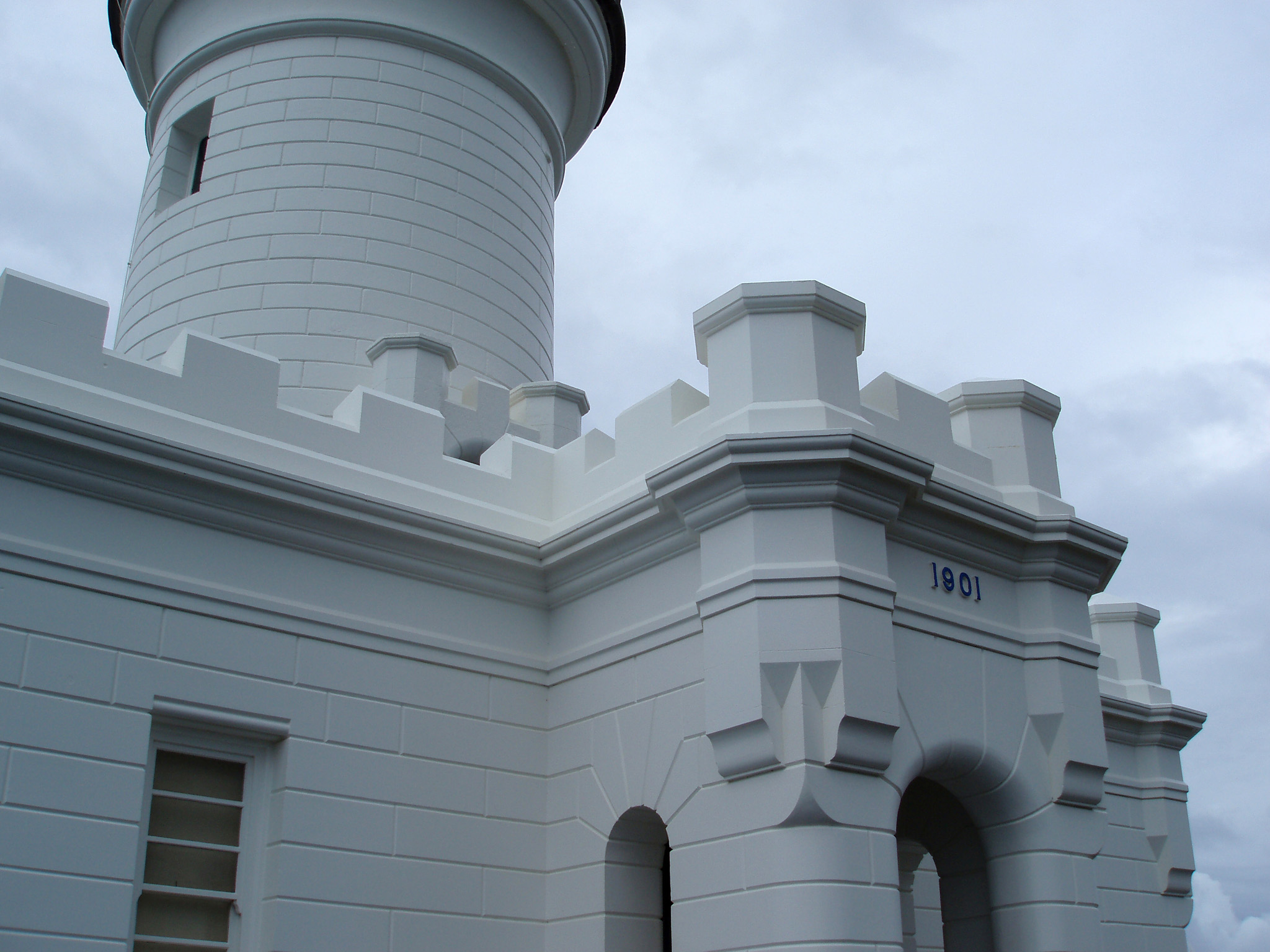Close up Vintage White Byron Bay Lighthouse Structure on Lighter Blue Gray Sky Background.