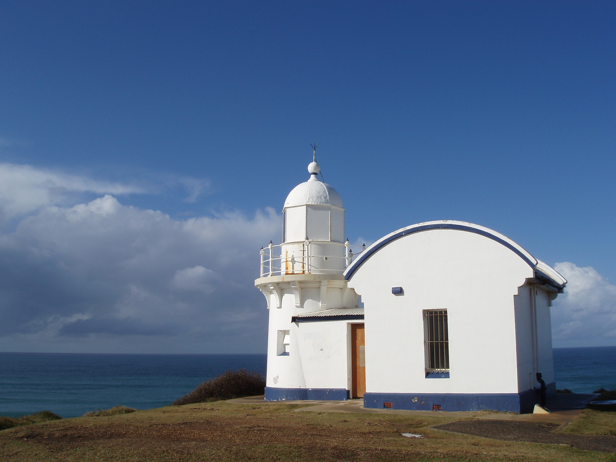 Vintage Style White Lighthouse Structure at Port Macquarie with Overlooking Beach View on Blue Sky Background.