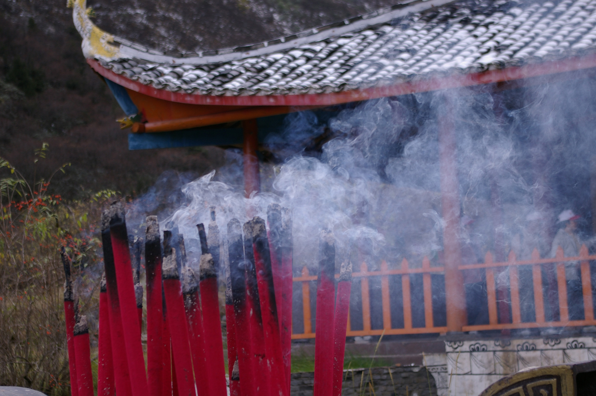 Burning incense sticks, or joss sticks, creating an aromatic smoke outside a Chinese temple