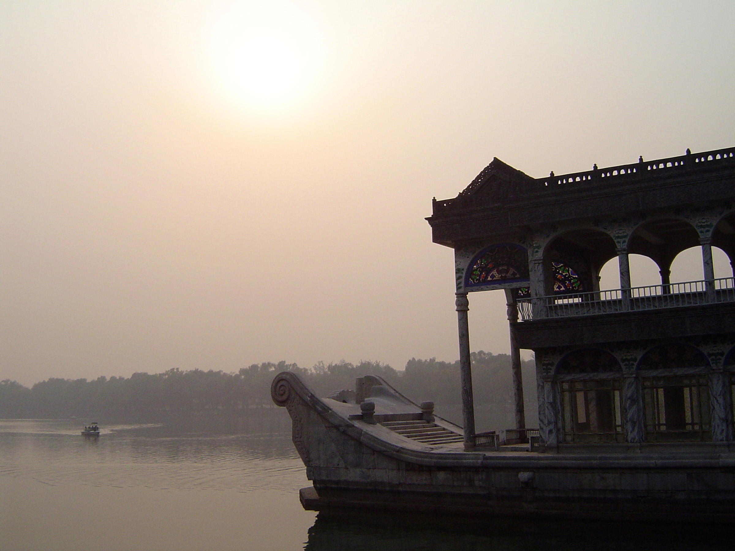 Ornate Chinese house boat with an upper arched covered viewing deck and living quarters below on a tranquil misty lake
