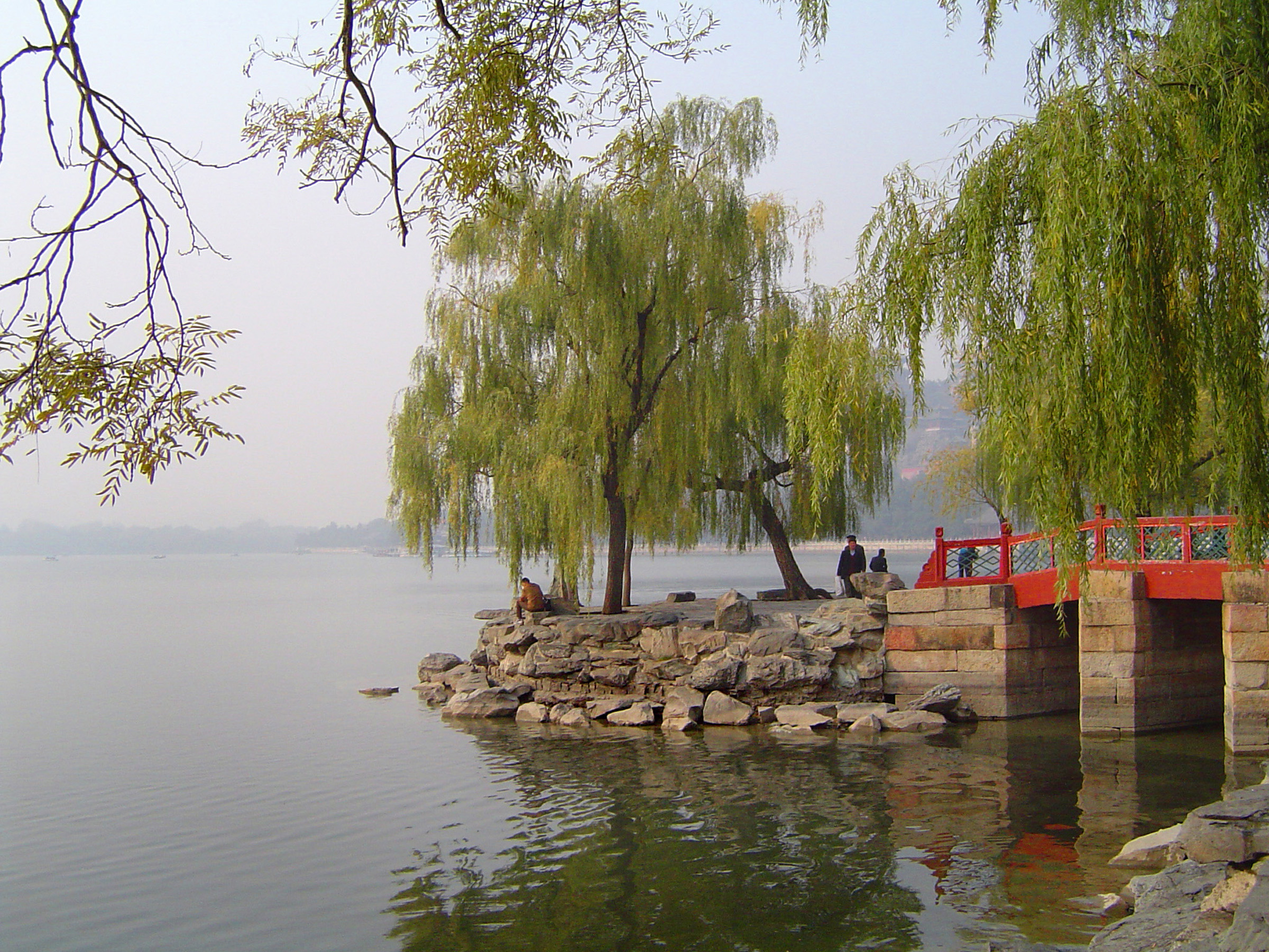 People standing under green weeping willow trees on a red wooden bridge to a stone headland on a tranquil scenic lake