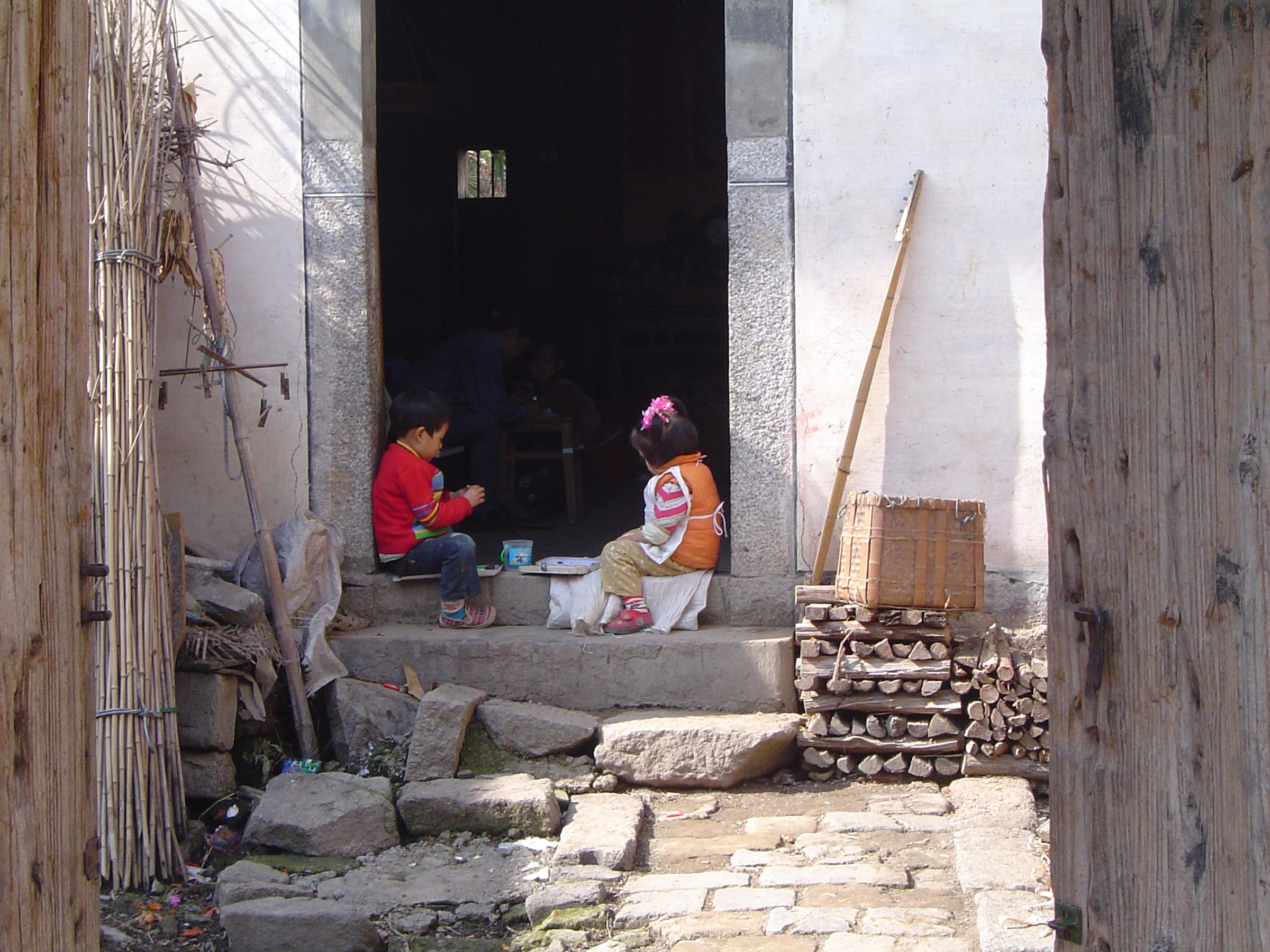 Two Kids Playing at the Door Step of Vintage Ordinary Chinese House in China.
