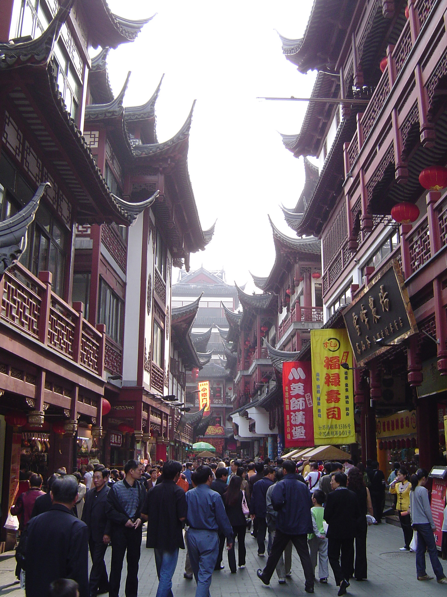 Random People at Ordinary Chinese Street with Huge Architectural Buildings Along the Sides.