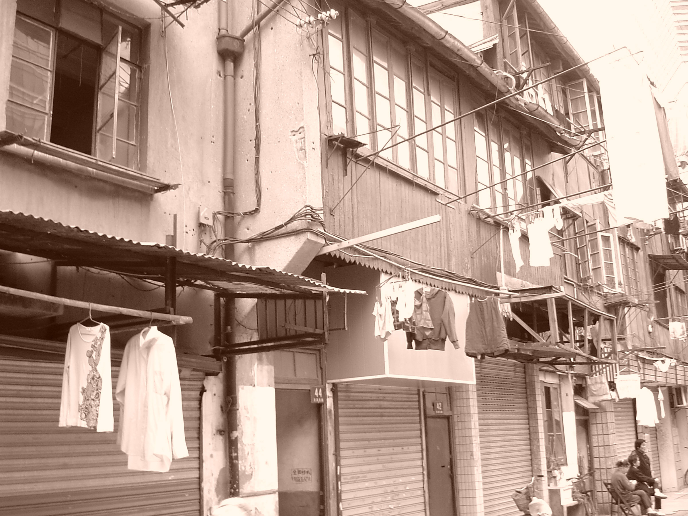 Sepia view of a typical Chinese street scene with residential apartments and washing hanging out to dry on the facades of buildings with people chatting in the street