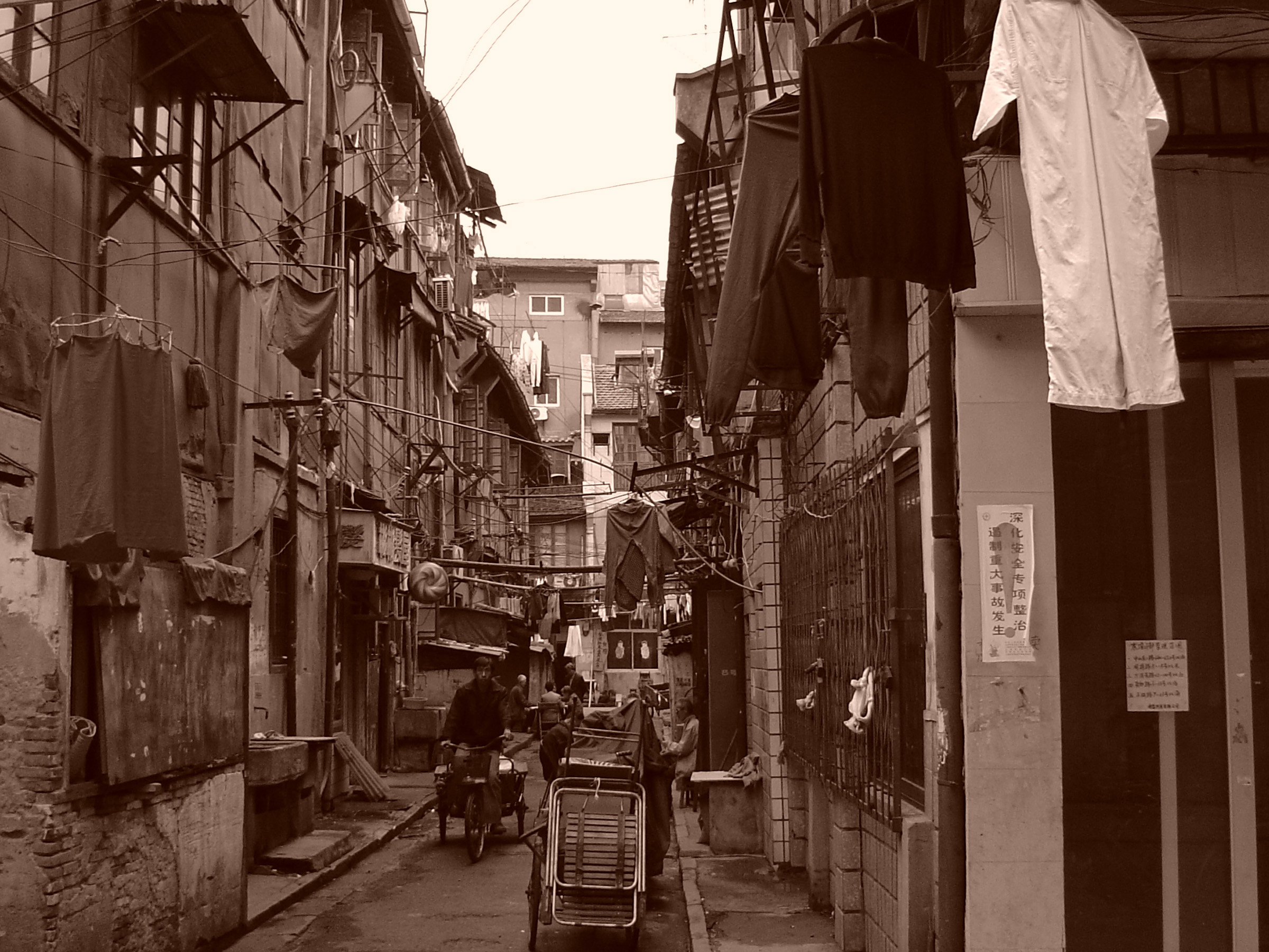 Vintage Ordinary Busy Chinese Street Scene at Poor Area with Big Houses on the Sides.