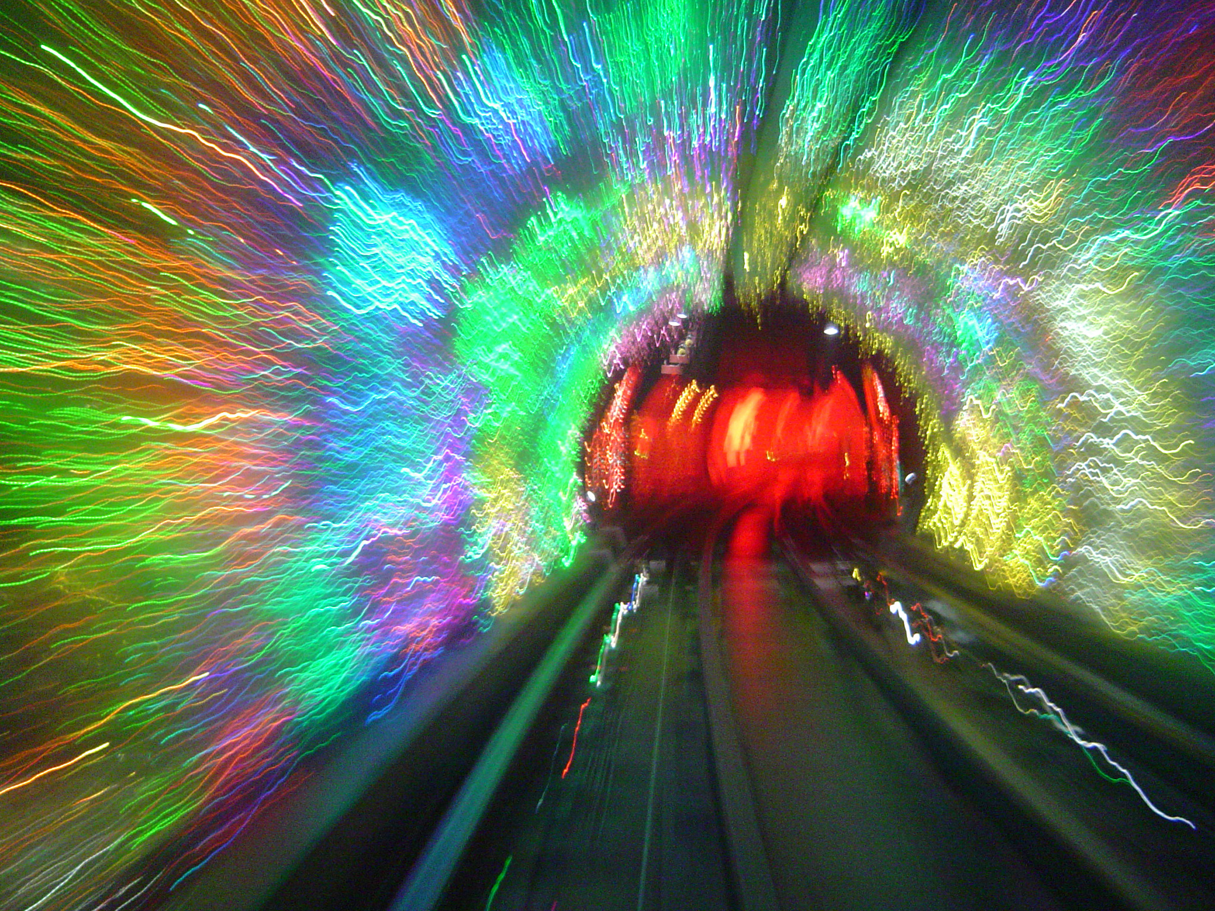 Colorful motion blur of a subway tunnel with red lights at the end