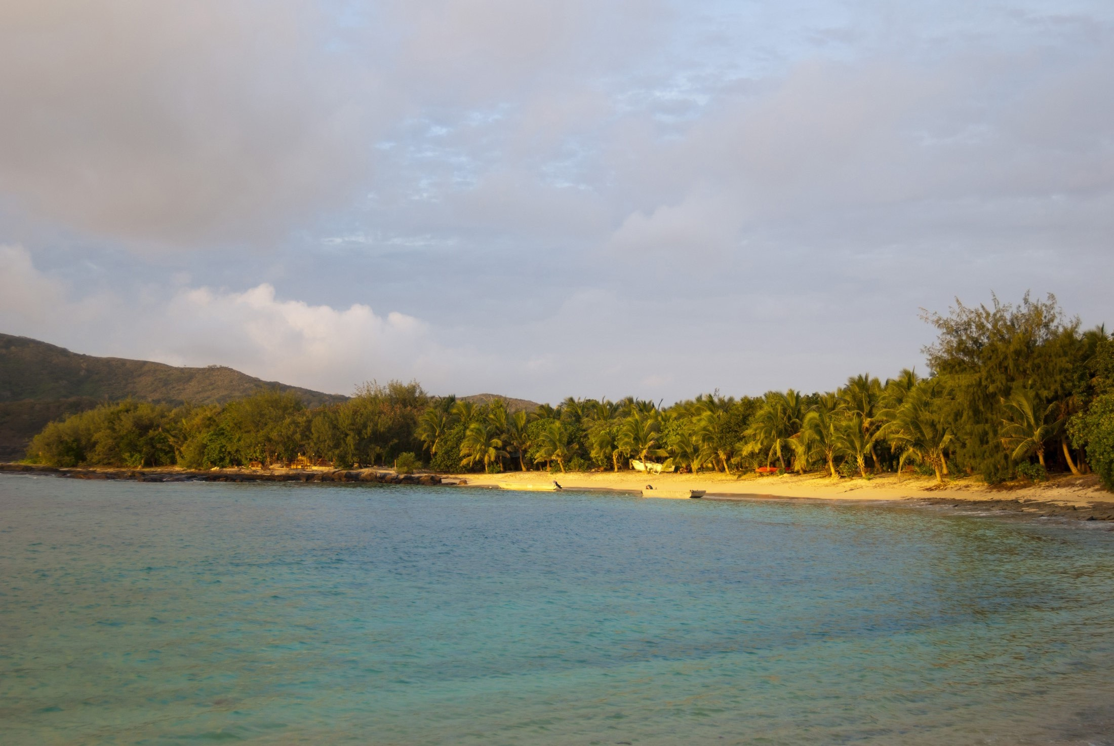 View over a calm sea to a sunset on a tropical beach with the golden glow lighting the sand and lush green vegetation