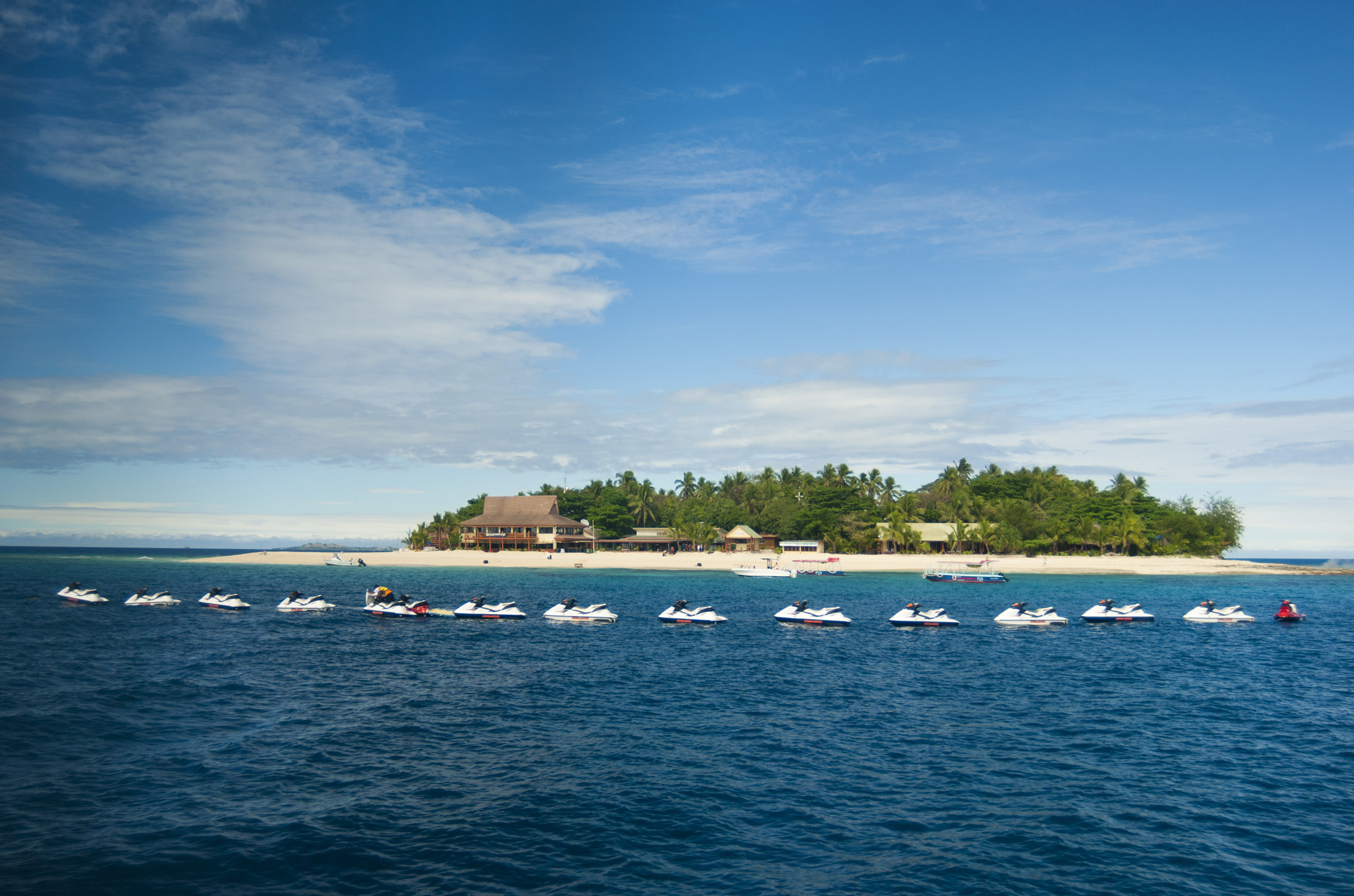 View across ocean of a line of jet skis moored in front of Beachcomber Island, Fiji with its small resort