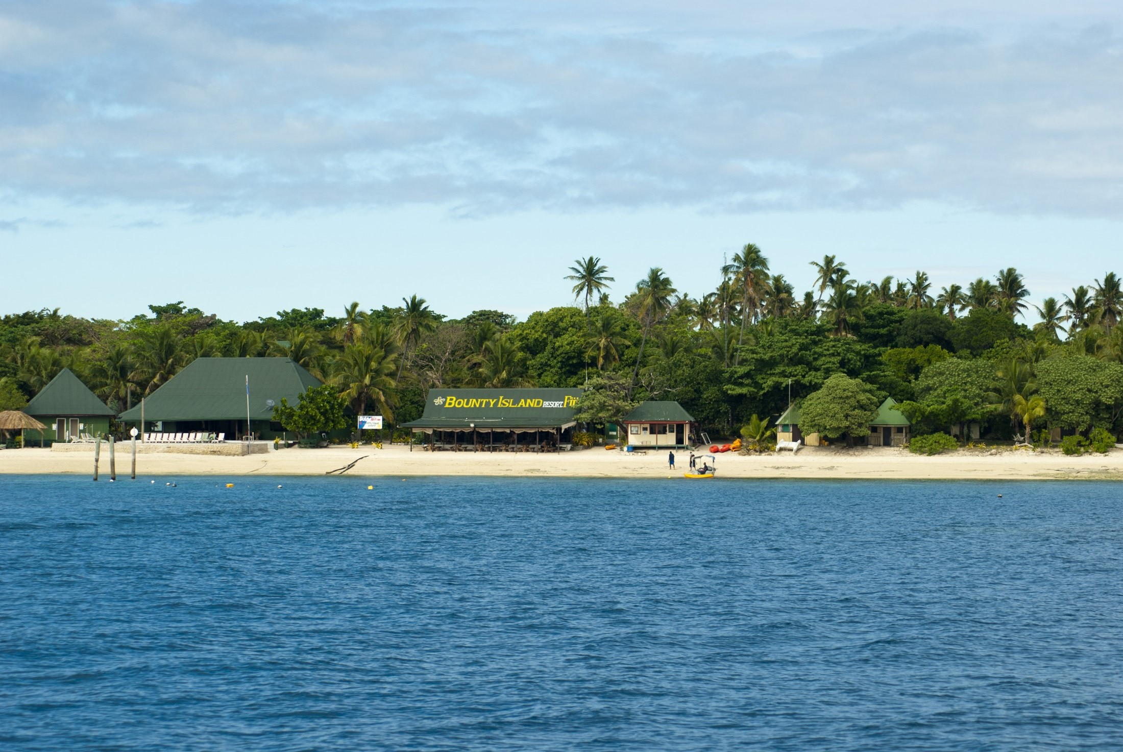 Bounty Island resort, Fiji, on an idyllic tropical island with tourist visible on the sandy beach in front of the buildings