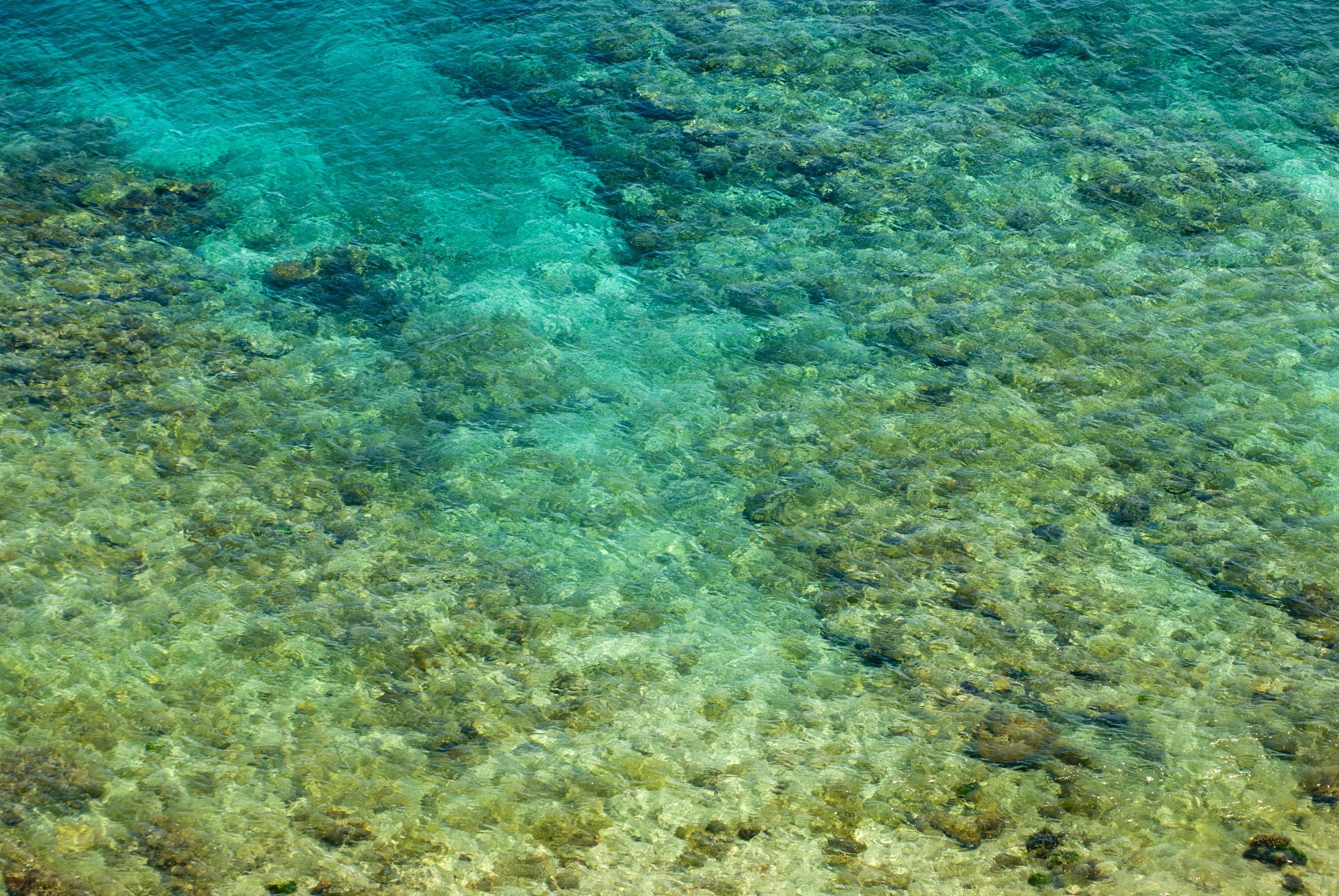 Abstract background of shallow crystal clear blue water with coral just offshore on a Fijian island