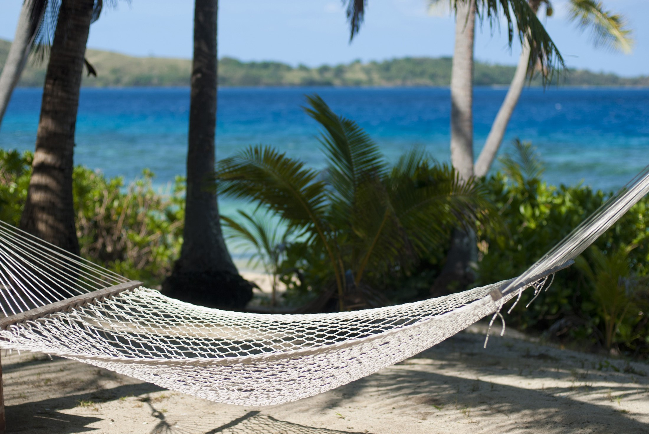 Beautiful scenic background of an empty hammock at a tropical beach overlooking the blue ocean