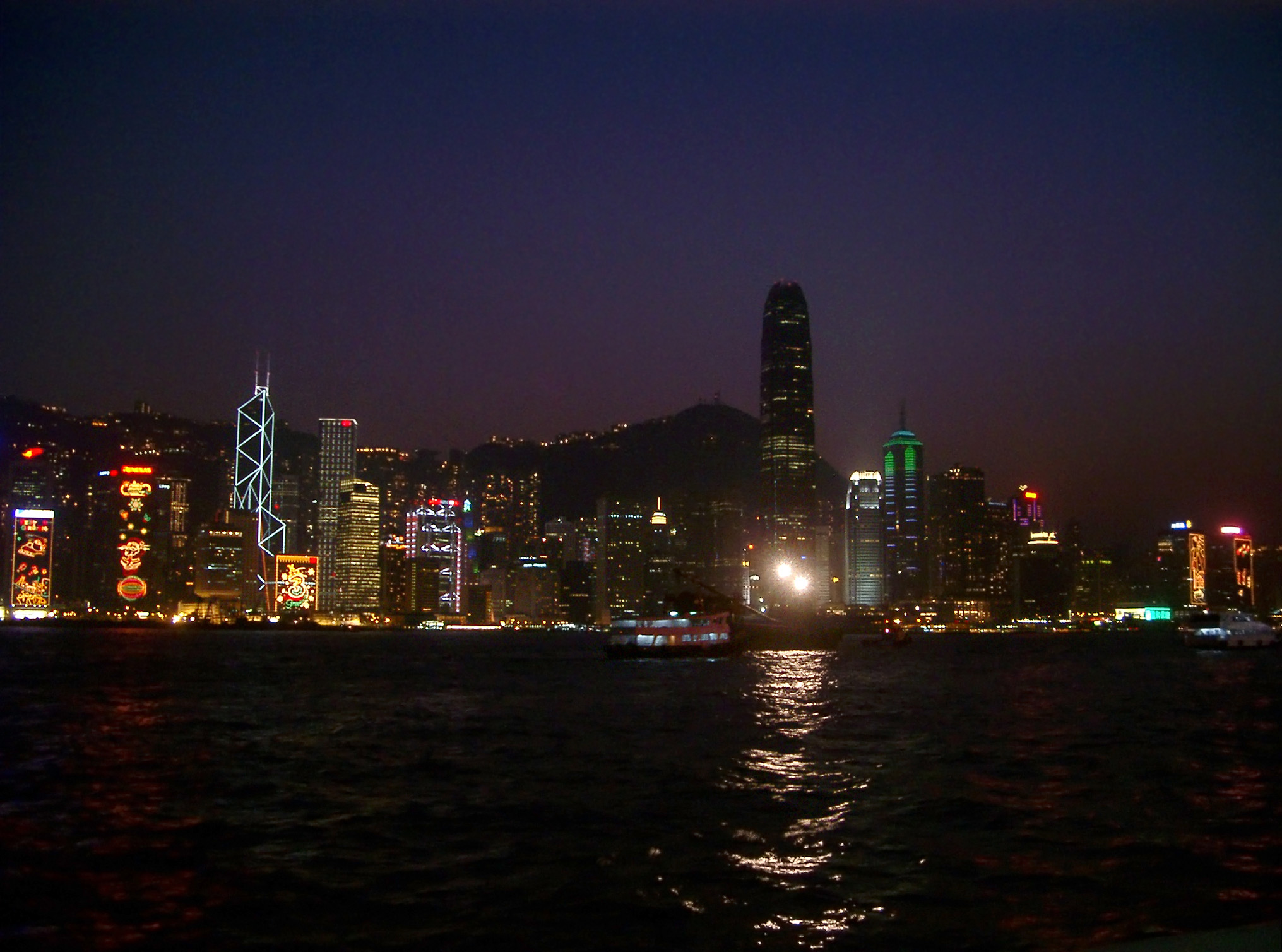 Cityscape of Kong at night with the buildings of the CBD illuminated and casting reflections across the water
