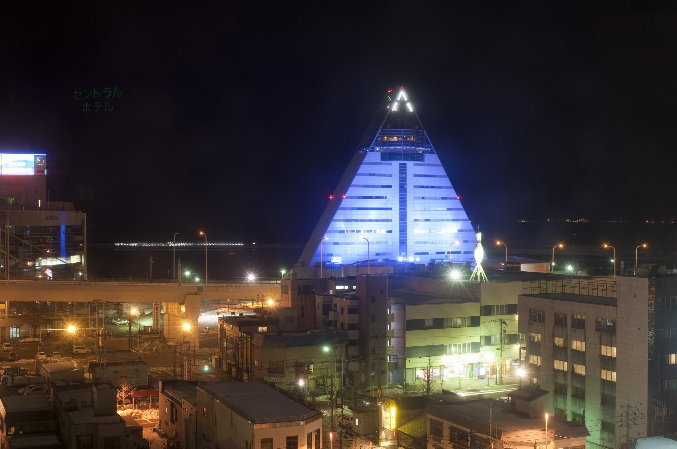 The landmark triangular pyramid like building of the Aomori Prefectural Tourist Center illuminated in blue at night