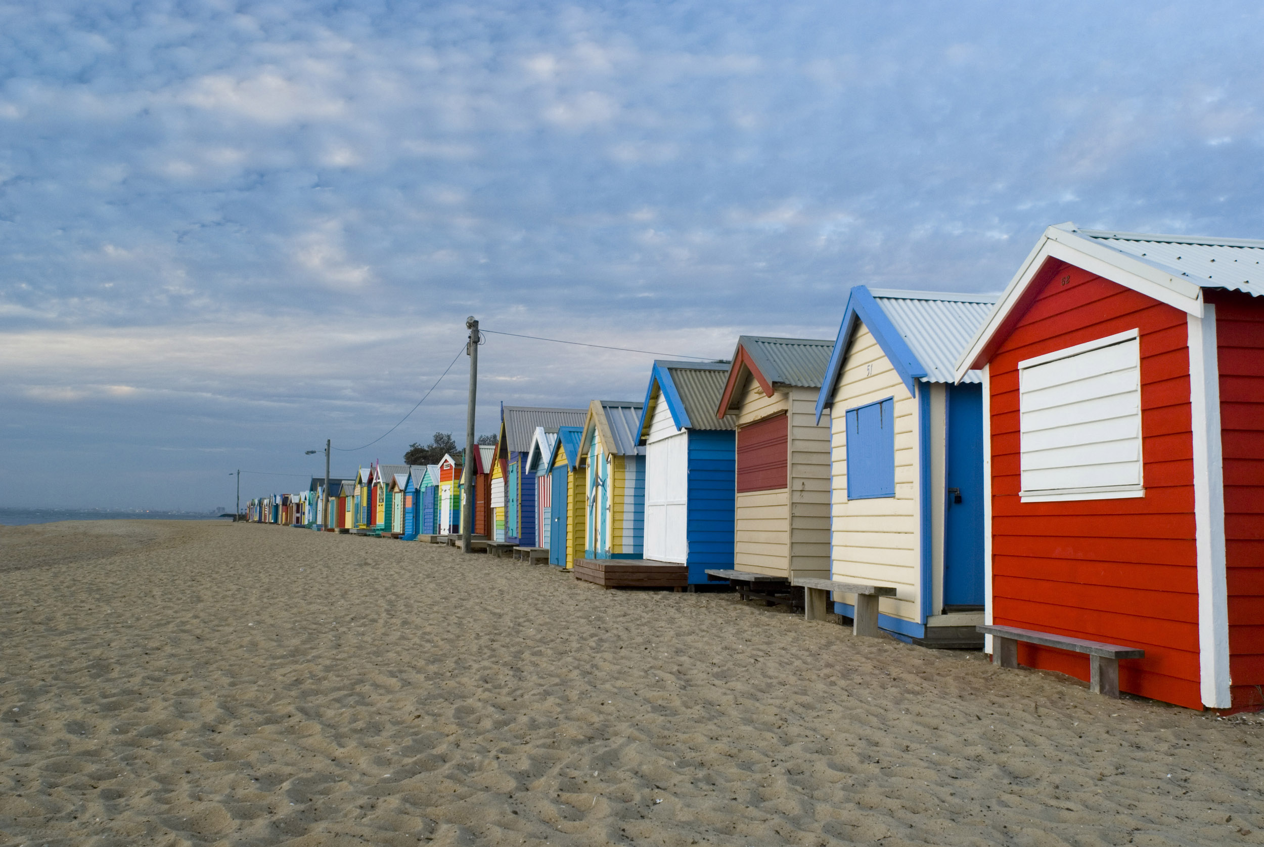 A series of empty, rustic beach huts and shacks on a deserted beach in Brighton near Melbourne, Australia.