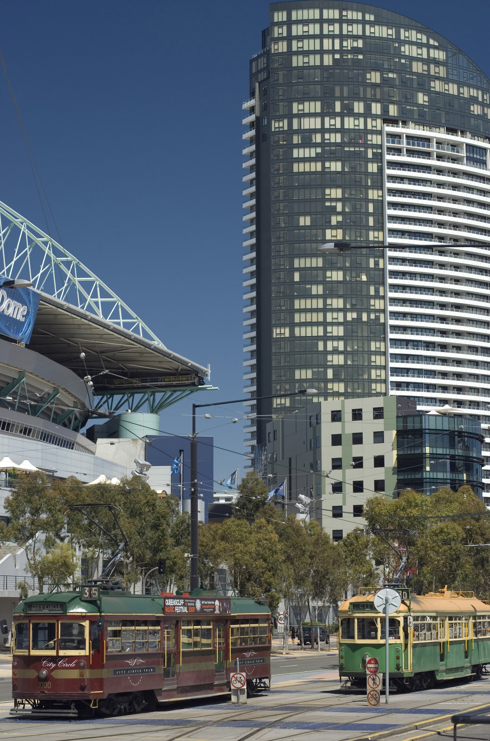 The Telstra Dome in The Docklands, Melbourne, Australia with street trams and a skyscraper in a busy street scene