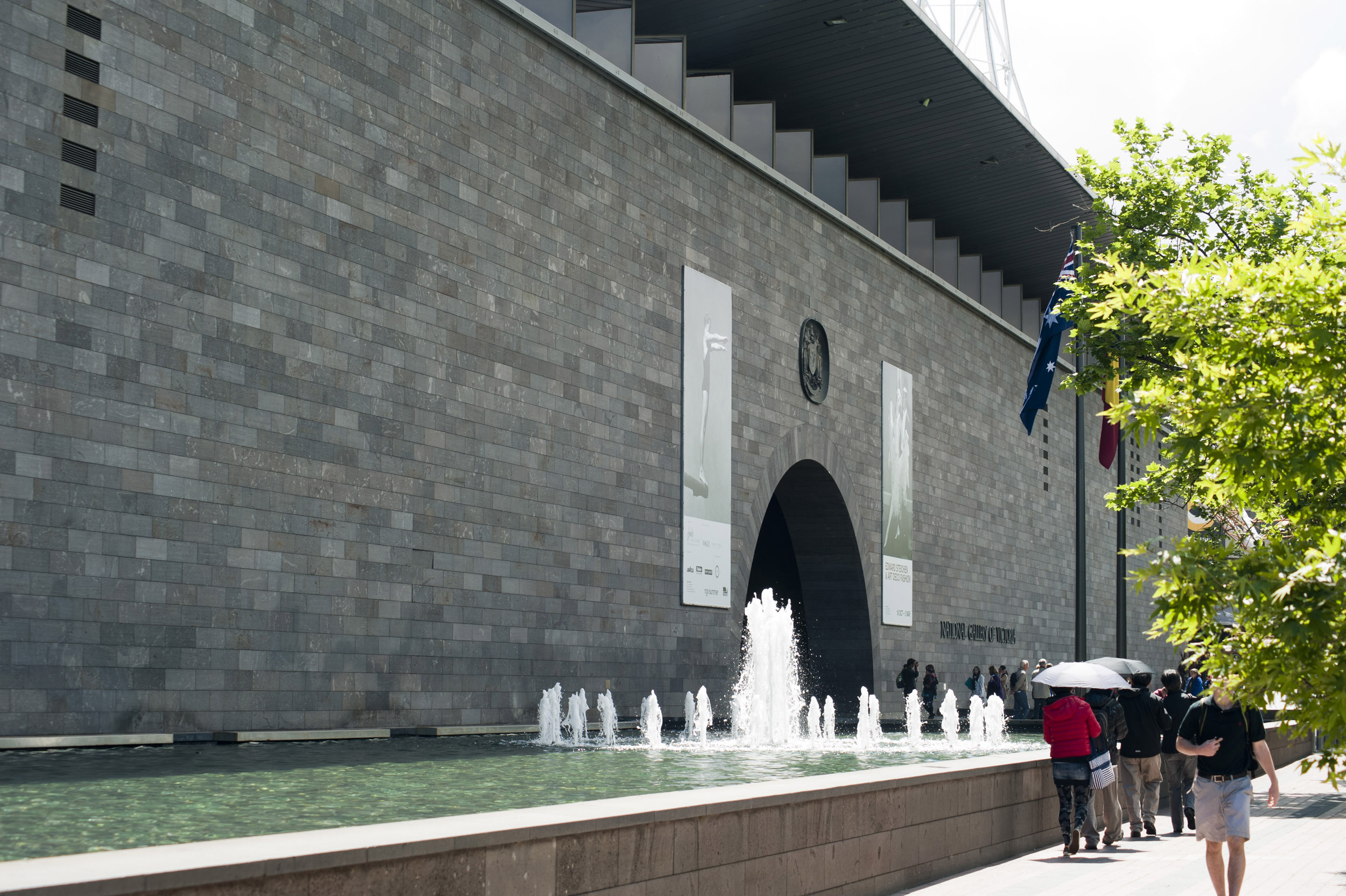 People outside the Melbourne National Gallery, Australia walking alongside the ornamental fountains and pond under umbrellas on a hot sunny day