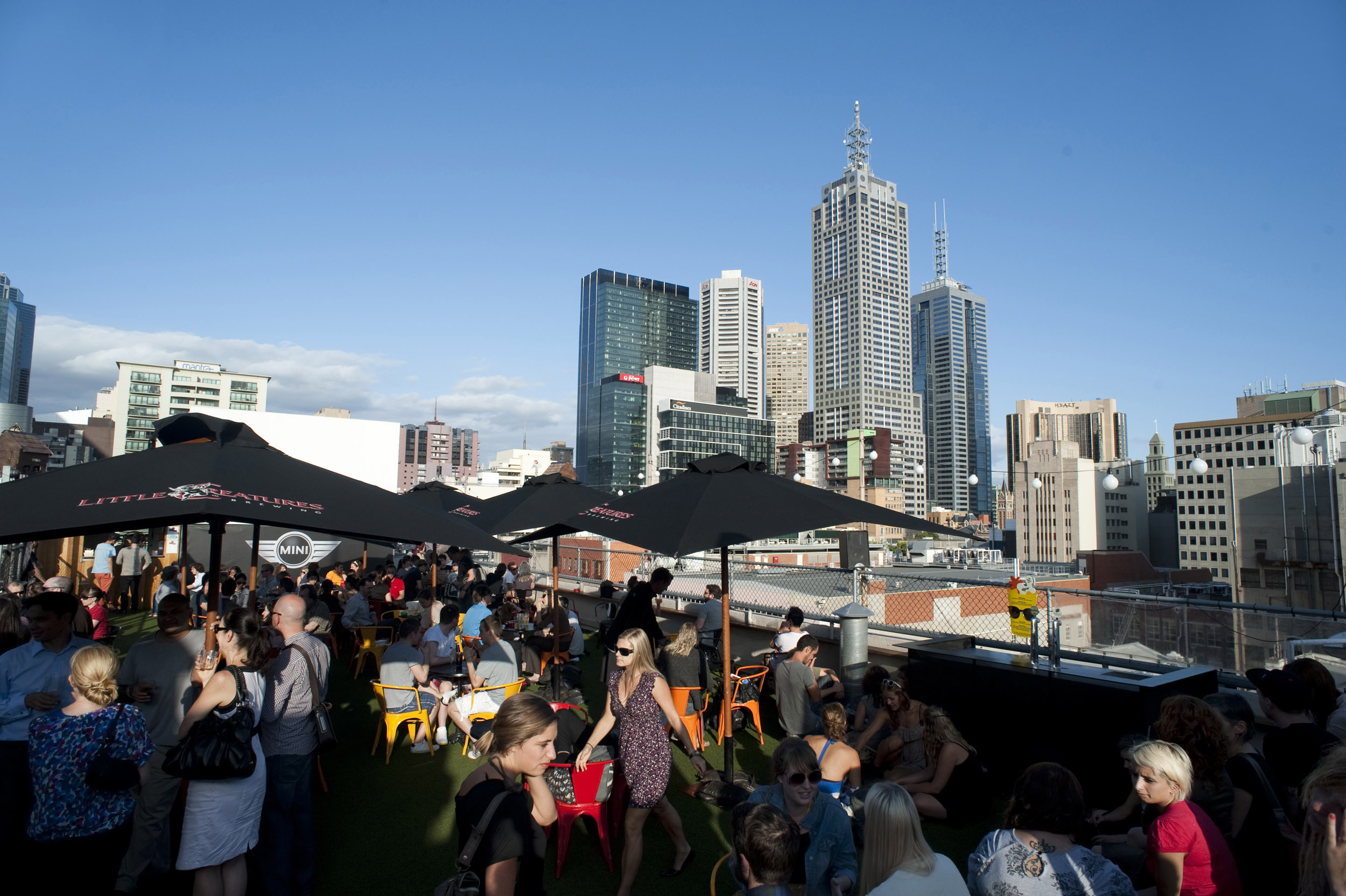 A bustling, busy rooftop bar on a clear, blue day in the centre of Melbourne city, Australia.