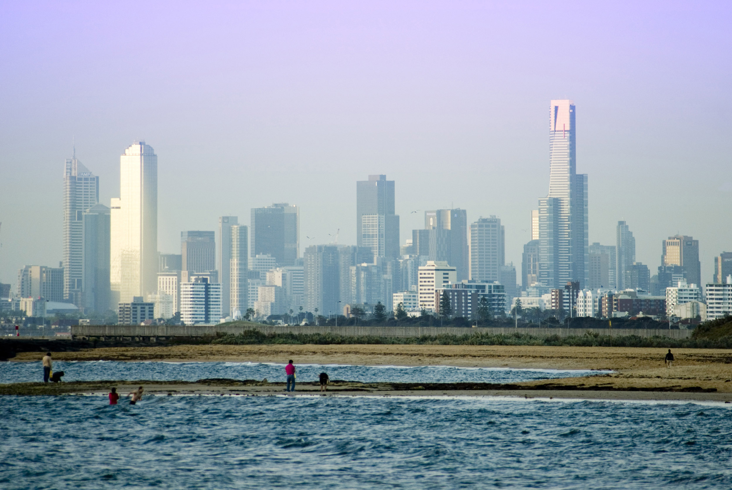 The distant Melbourne city skyline and CBD buildings from a beautiful, quiet suburban ocean beach.