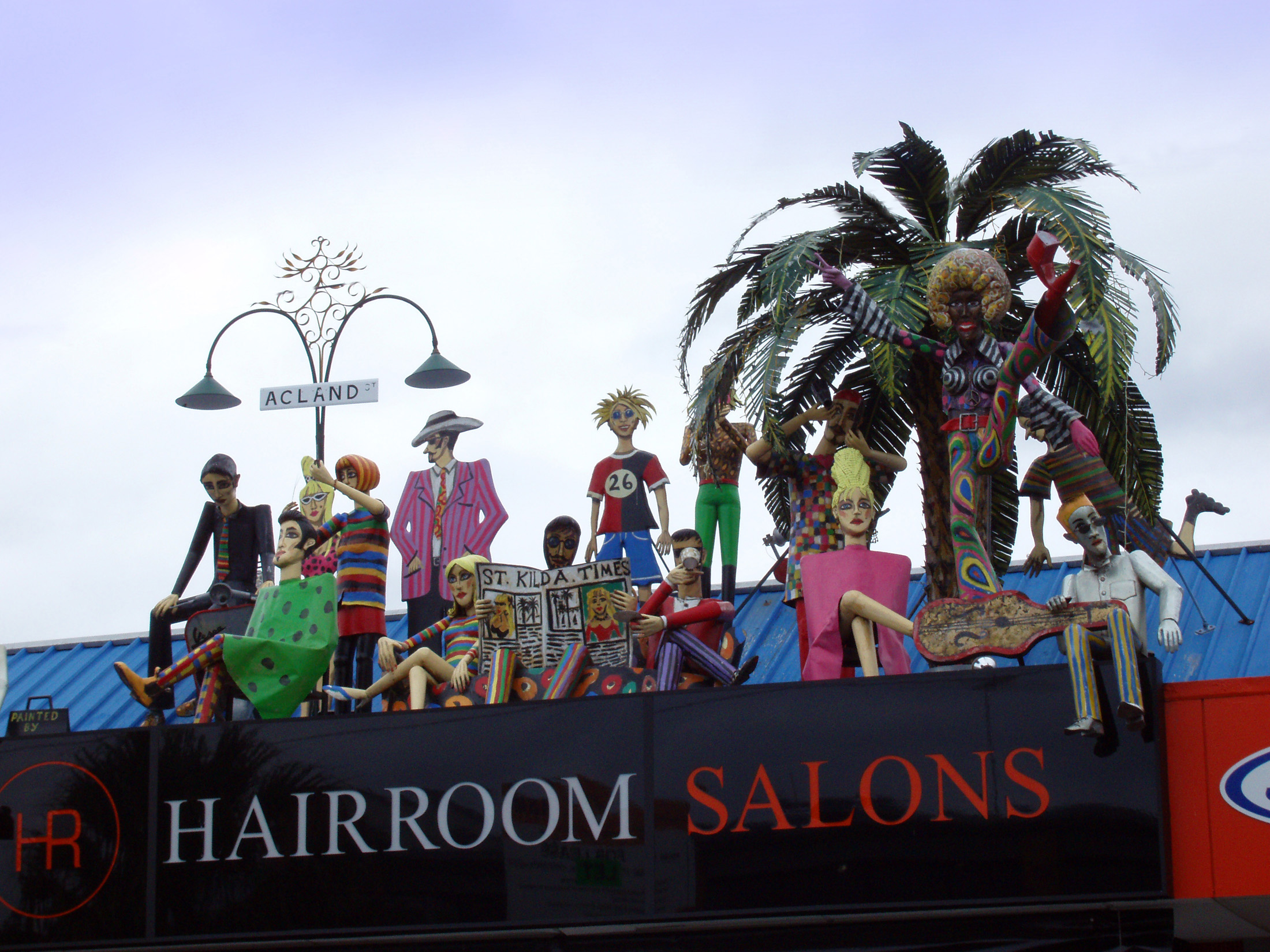 Hairroom Salon Building Signage with Artistic Human Sculptures on Rooftop at St Kilda in Melbourne, Australia.