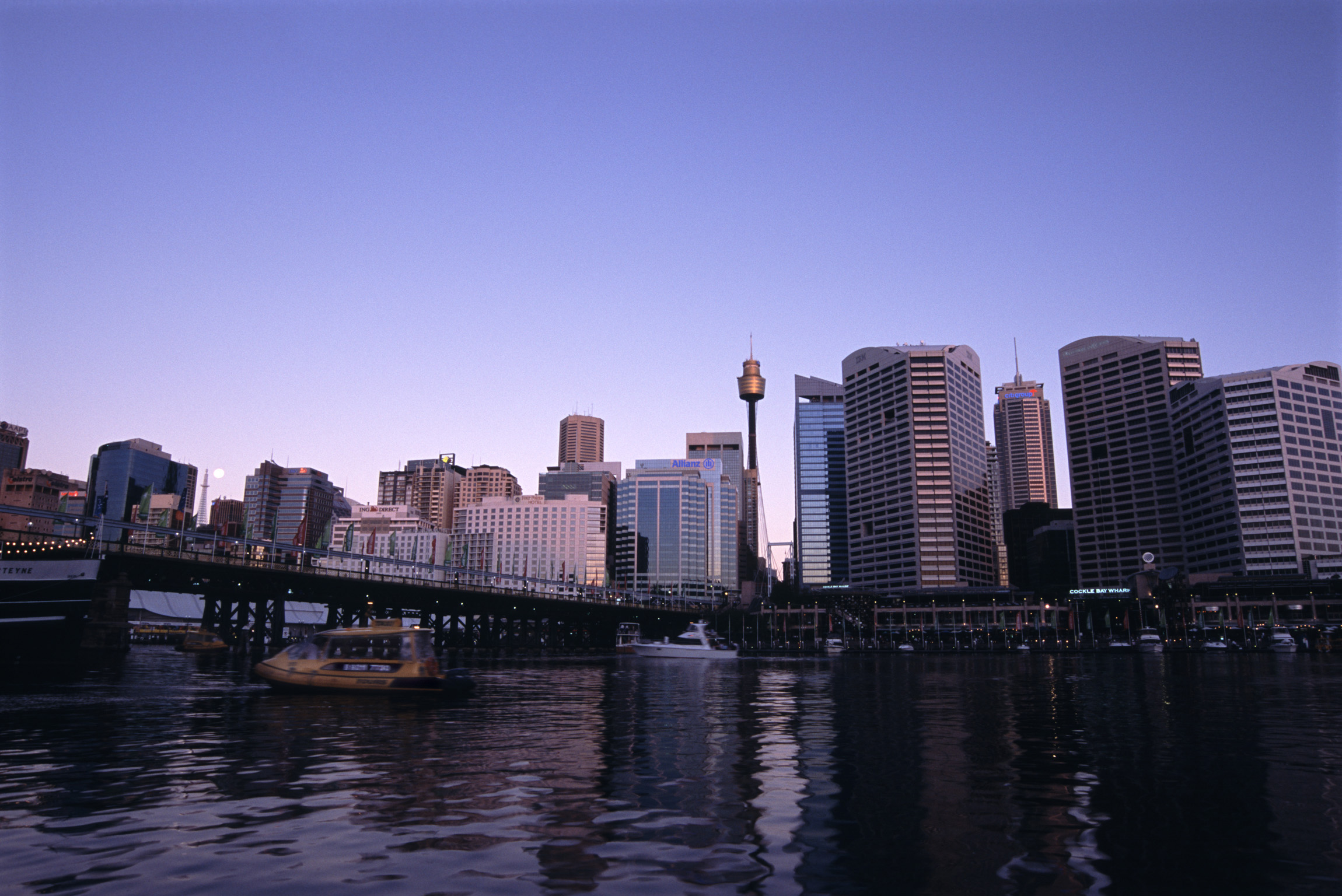 Beautiful Australian Cityscape - Darling Harbour Looking Towards the East. Captured with Architectural Buildings, Bridge and Boats on Gradient Blue Sky Background.