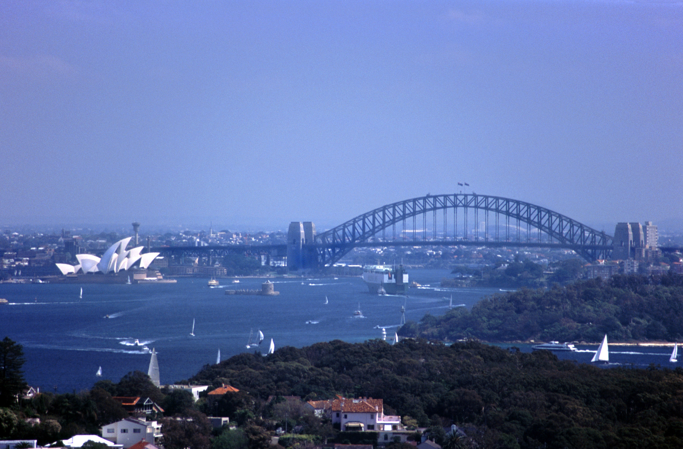 View of Sydney Harbour with the Opera House and Sydney Harbour Bridge on a hot blue sky summer day