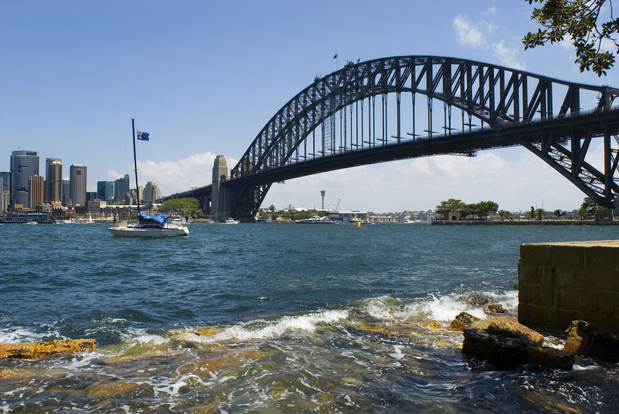 A panoramic view of the Sydney harbour bridge, boats and city on a beautiful, clear, blue sunny day.