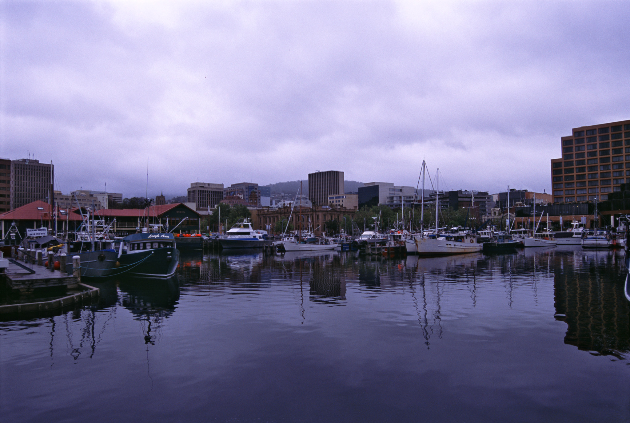Hobart harbor, Tasmania on the Derwent River with a variety of ships and boats moored at the quays in sheltered water on a cloudy day
