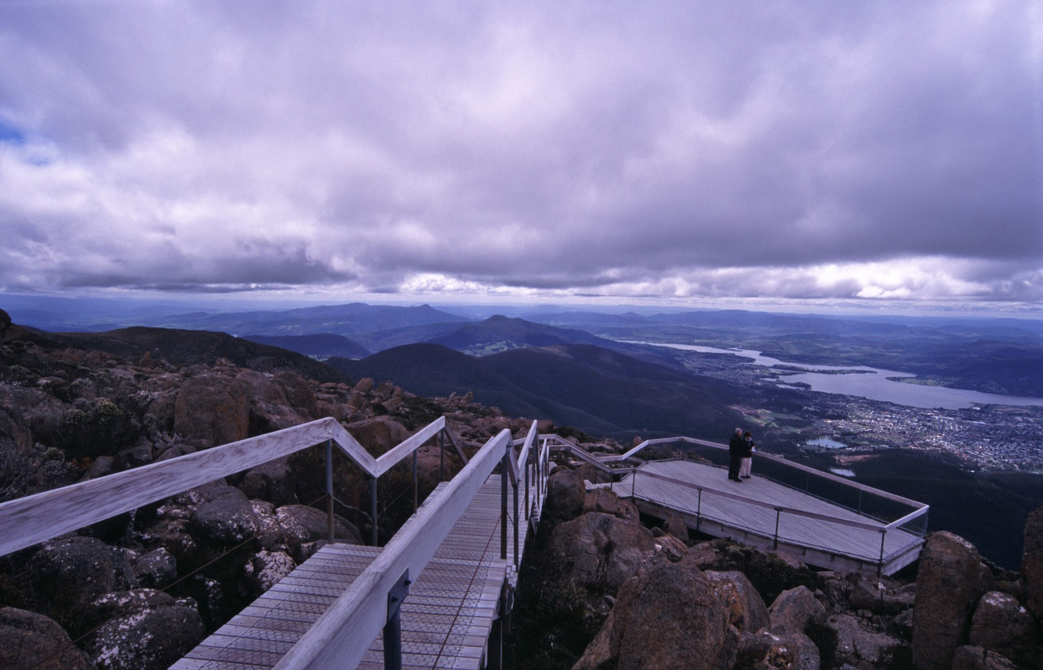 Lookout platform on Mount Wellington, Tasmania overlooking the Derwent River estuary and city of Hobart on a grey overcast day with a tourist at the viewing telescope