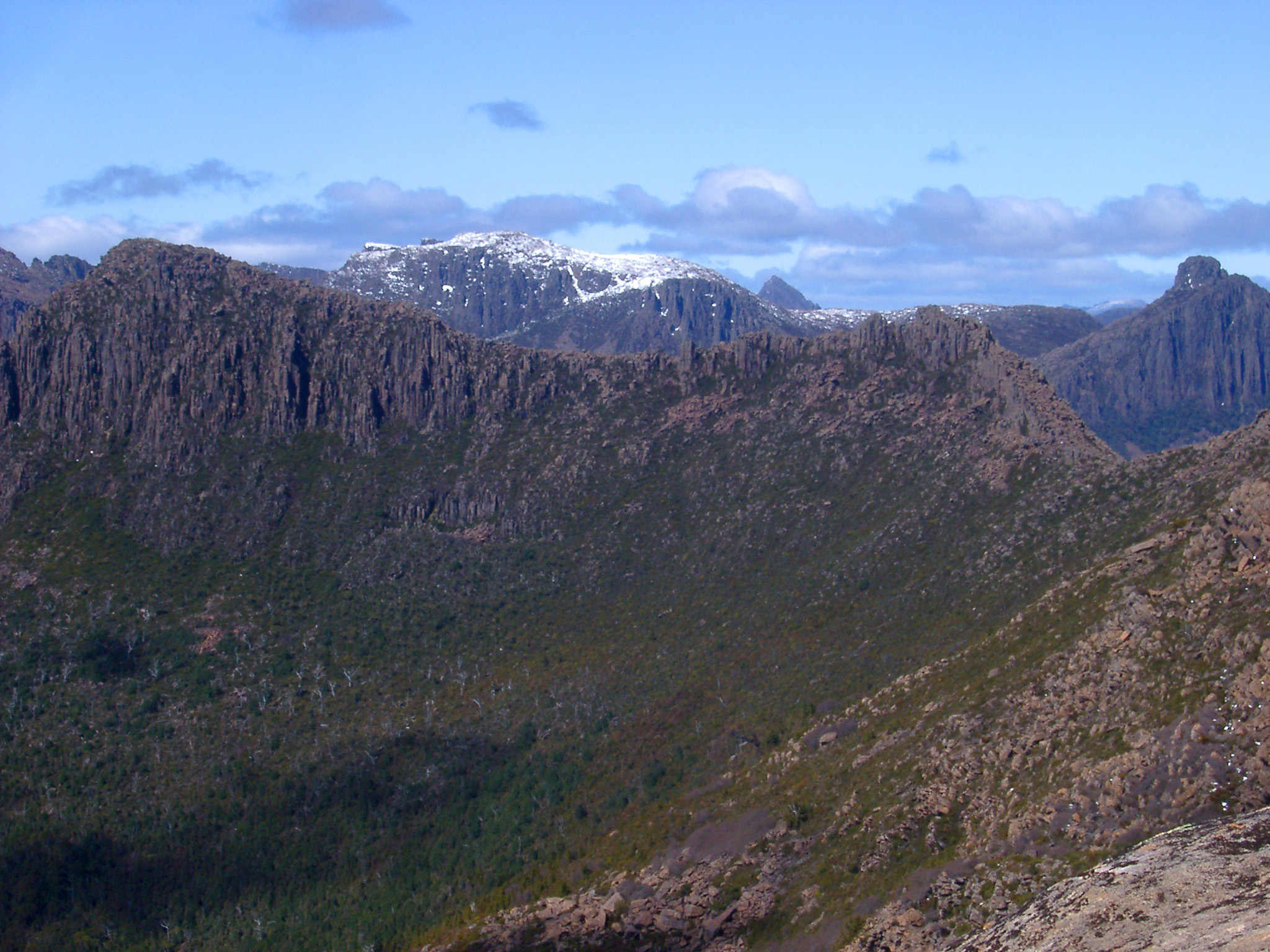 View from Mount Ossa, Tasmania, the highest peak in the heart of Cradle Mountain-Lake St Clair National Park with distant rugged mountain valleys and peaks with scattered snow