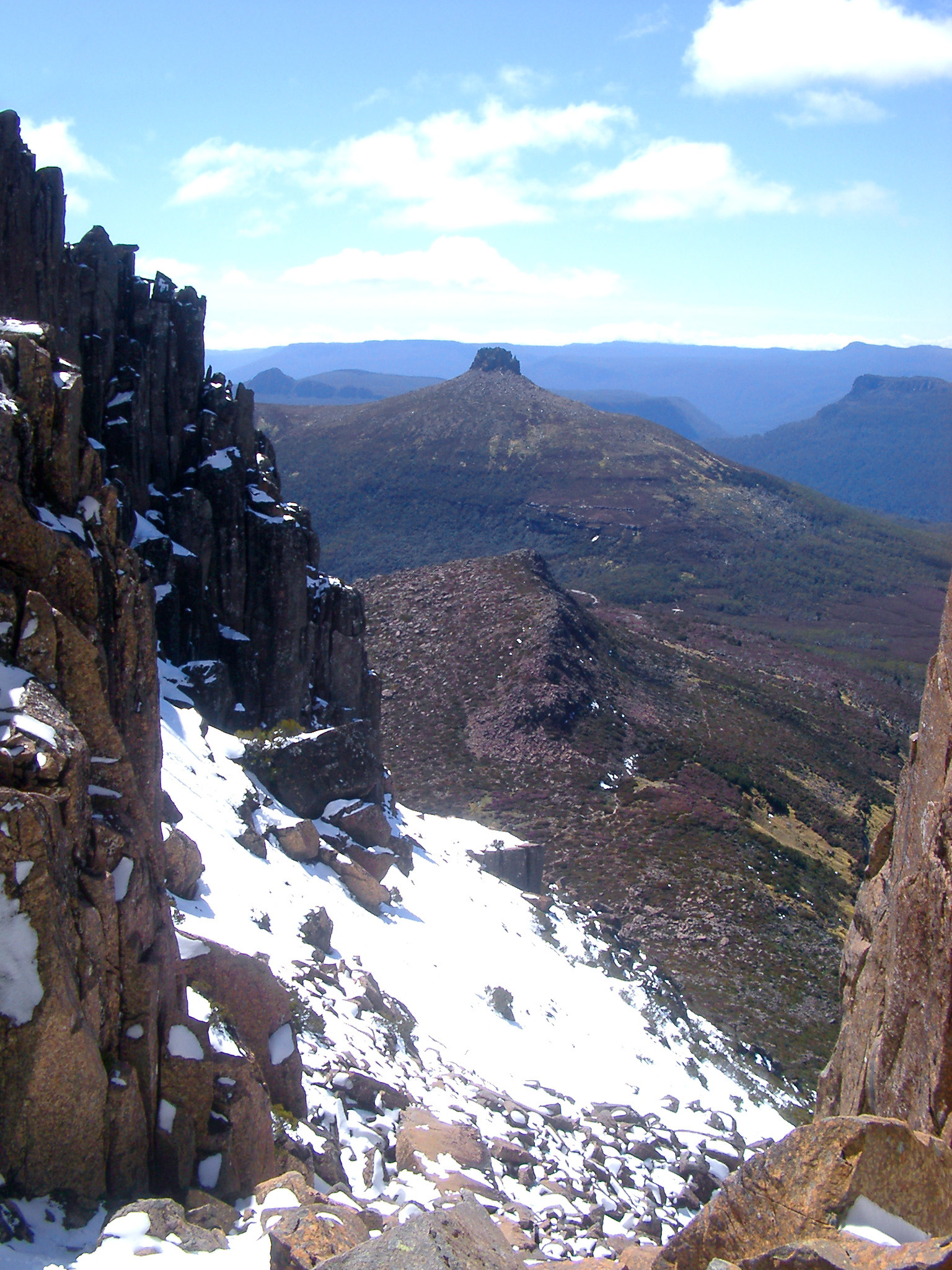 View from the highest mountain in Tasmania, Mount Ossa of the overland track crossing the mountains dusted with light snow