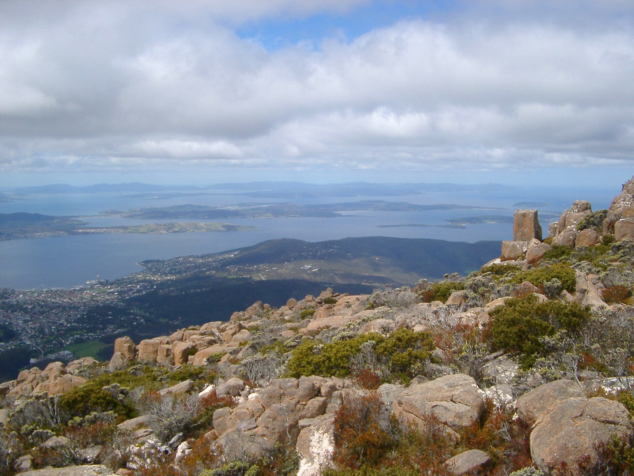 View from the summit of Mount Wellington, Tasmania of the Derwent River estuary and city of Hobart under a cloudy blue sky